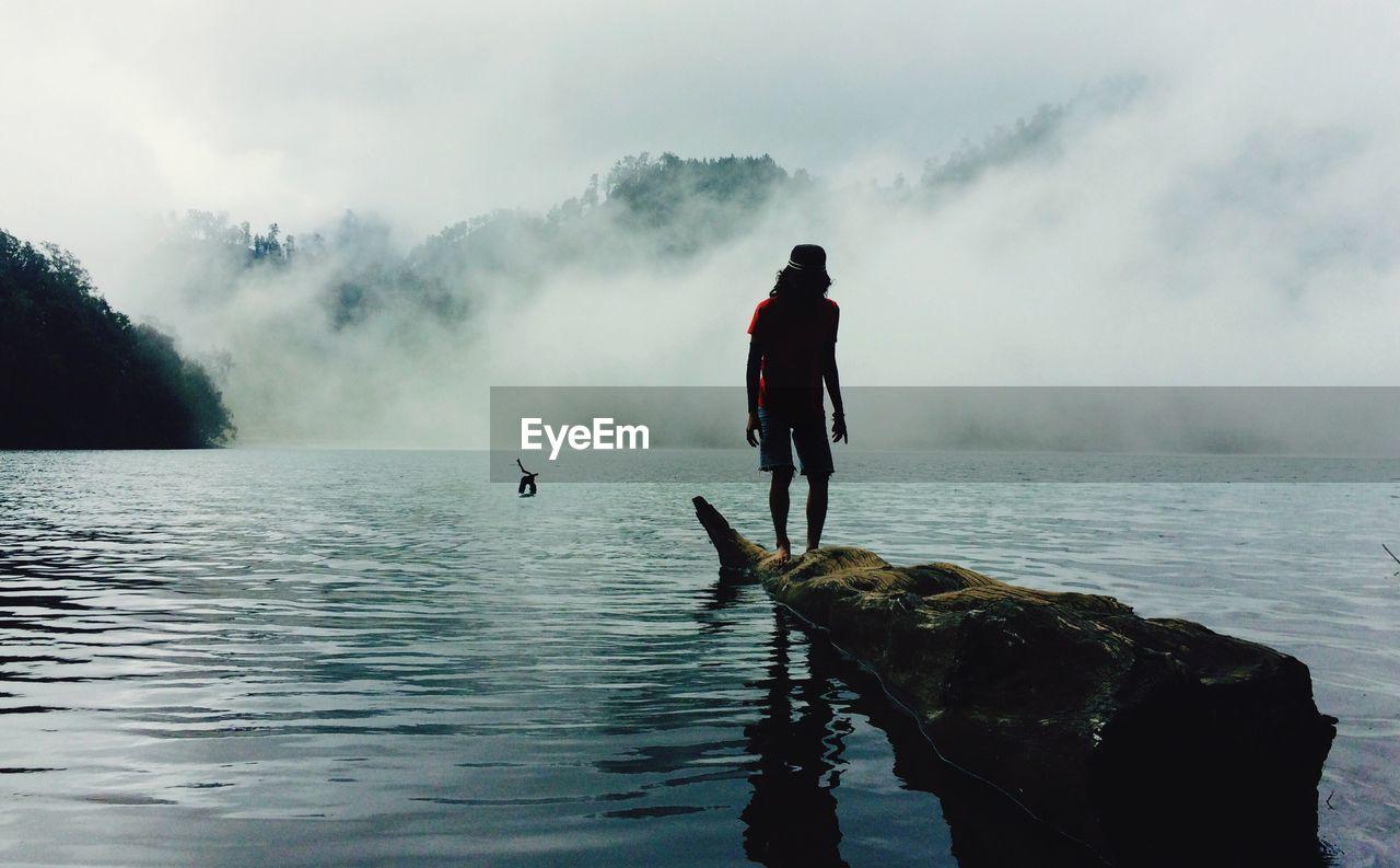 Man standing on log over ranu kumbolo lake during foggy weather
