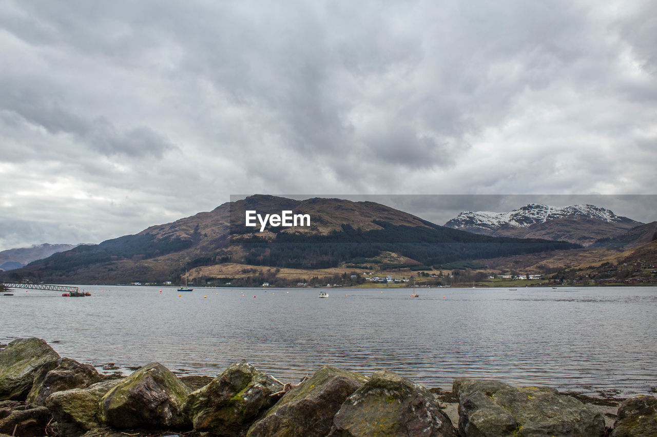 Calm lake against rocky mountain range