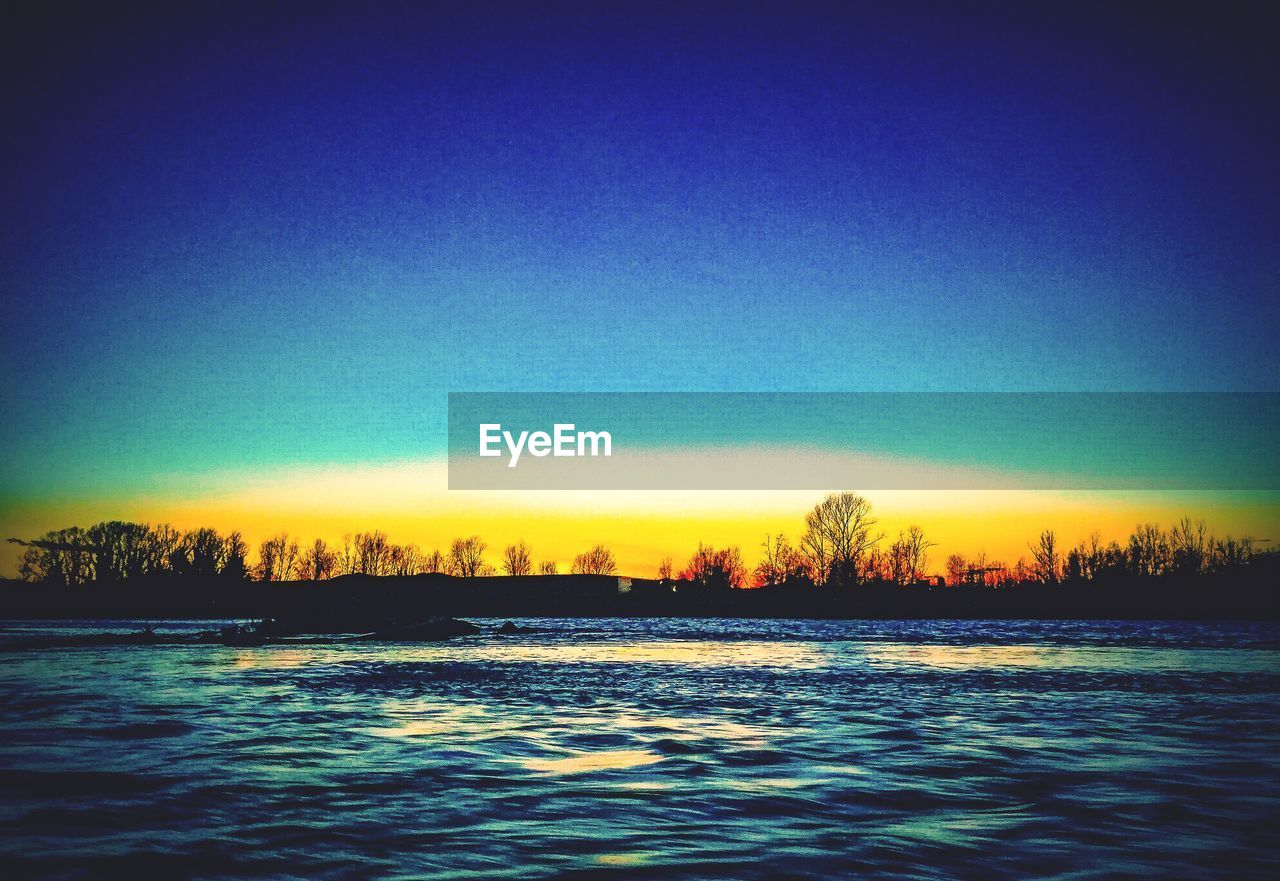 nature, water, tranquility, beauty in nature, waterfront, no people, tranquil scene, sunset, scenics, outdoors, tree, clear sky, blue, silhouette, cold temperature, winter, sky, view into land, day
