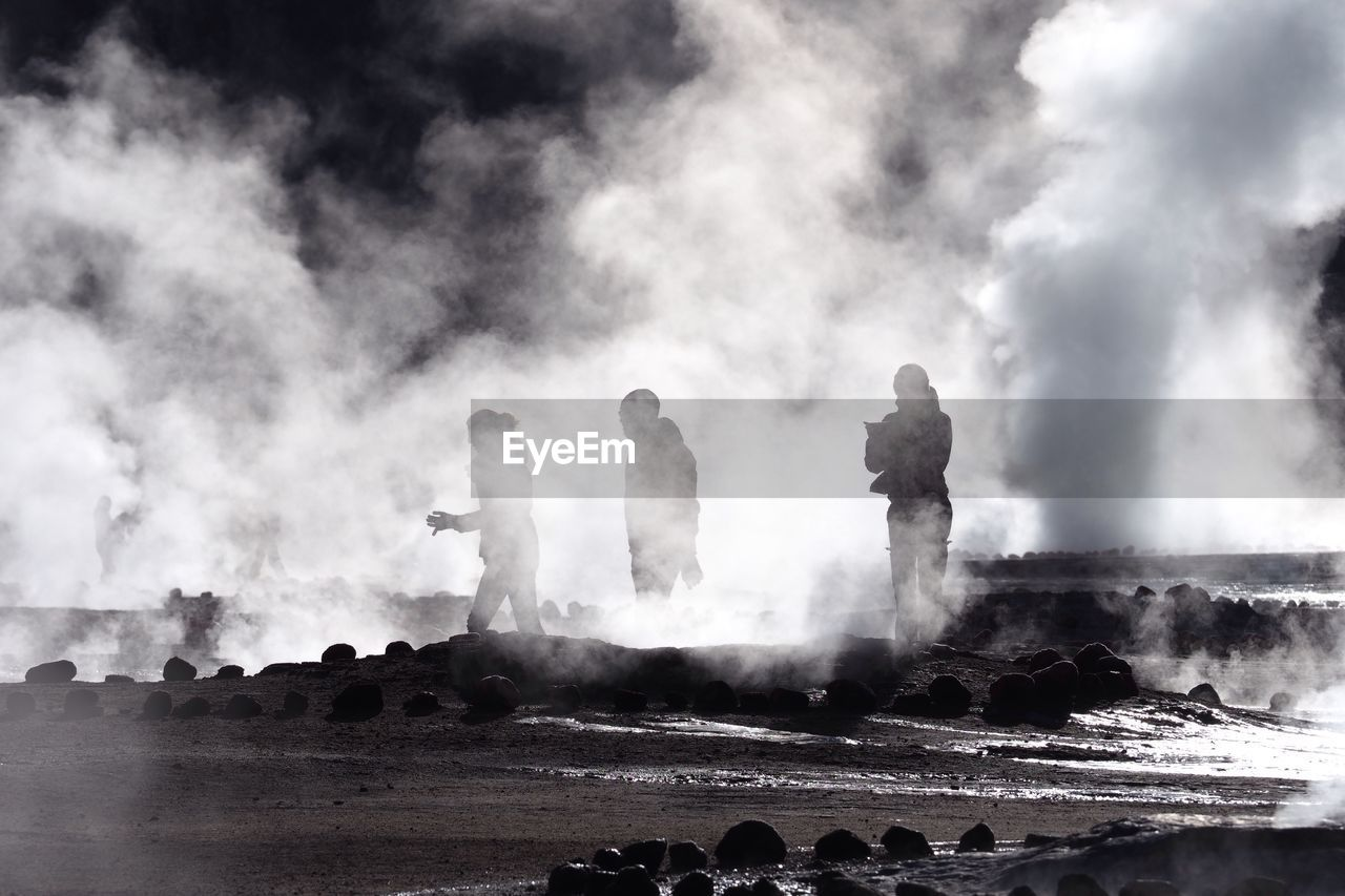 People At Volcanic Landscape Against Sky