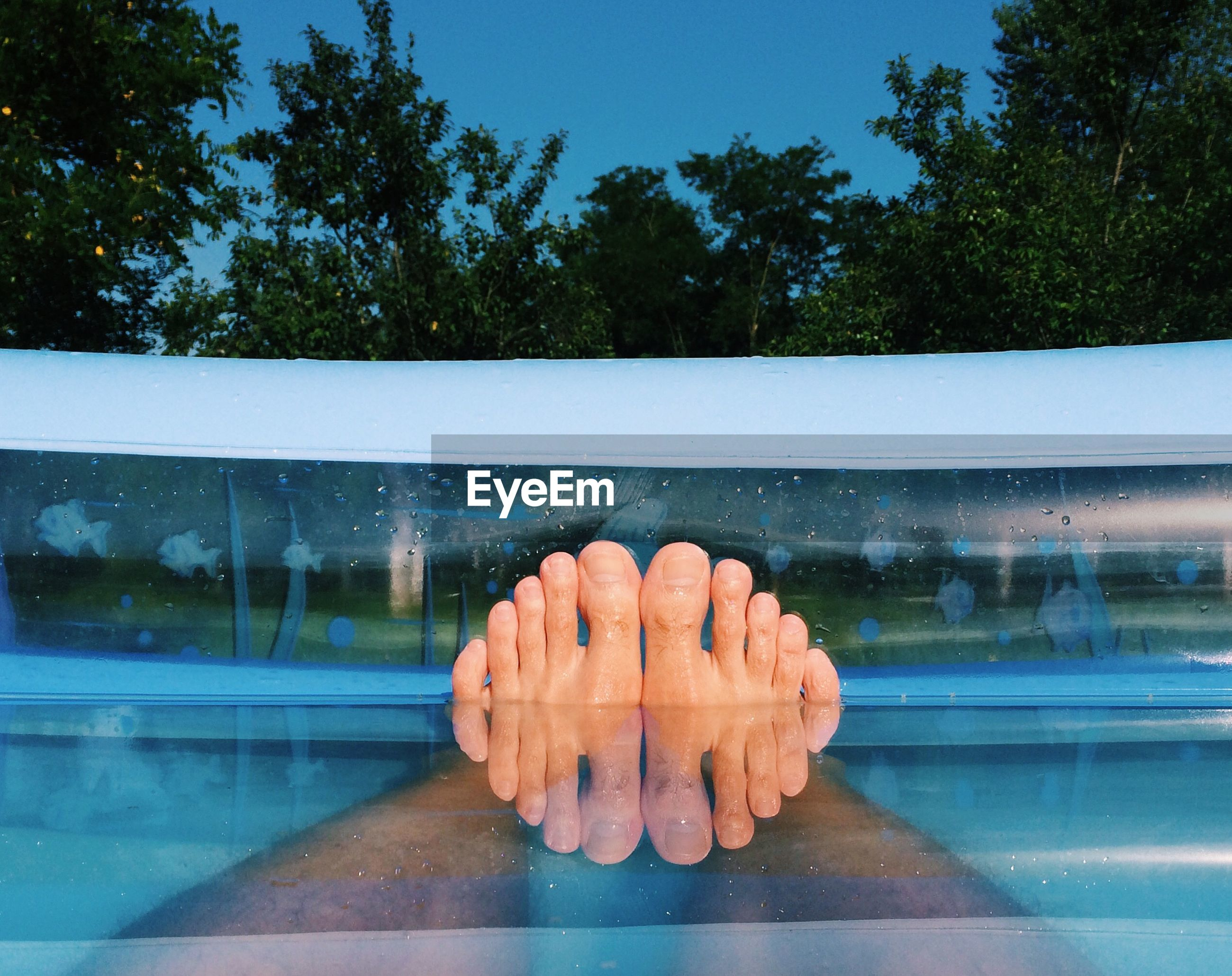 Low section of man legs in wading pool against sky