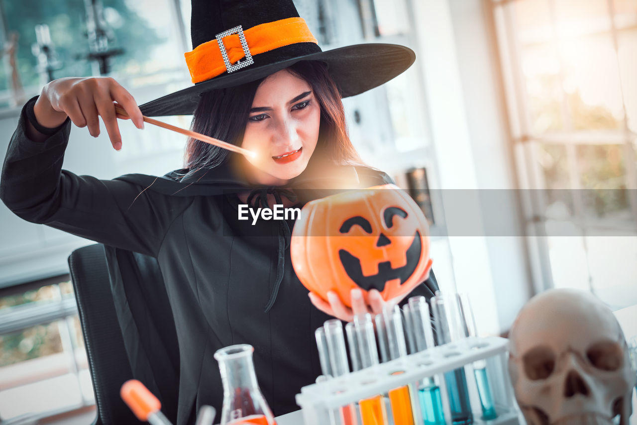 holding, real people, halloween, one person, front view, celebration, young adult, lifestyles, young women, women, leisure activity, indoors, focus on foreground, jack o' lantern, portrait, orange color, food and drink, witch