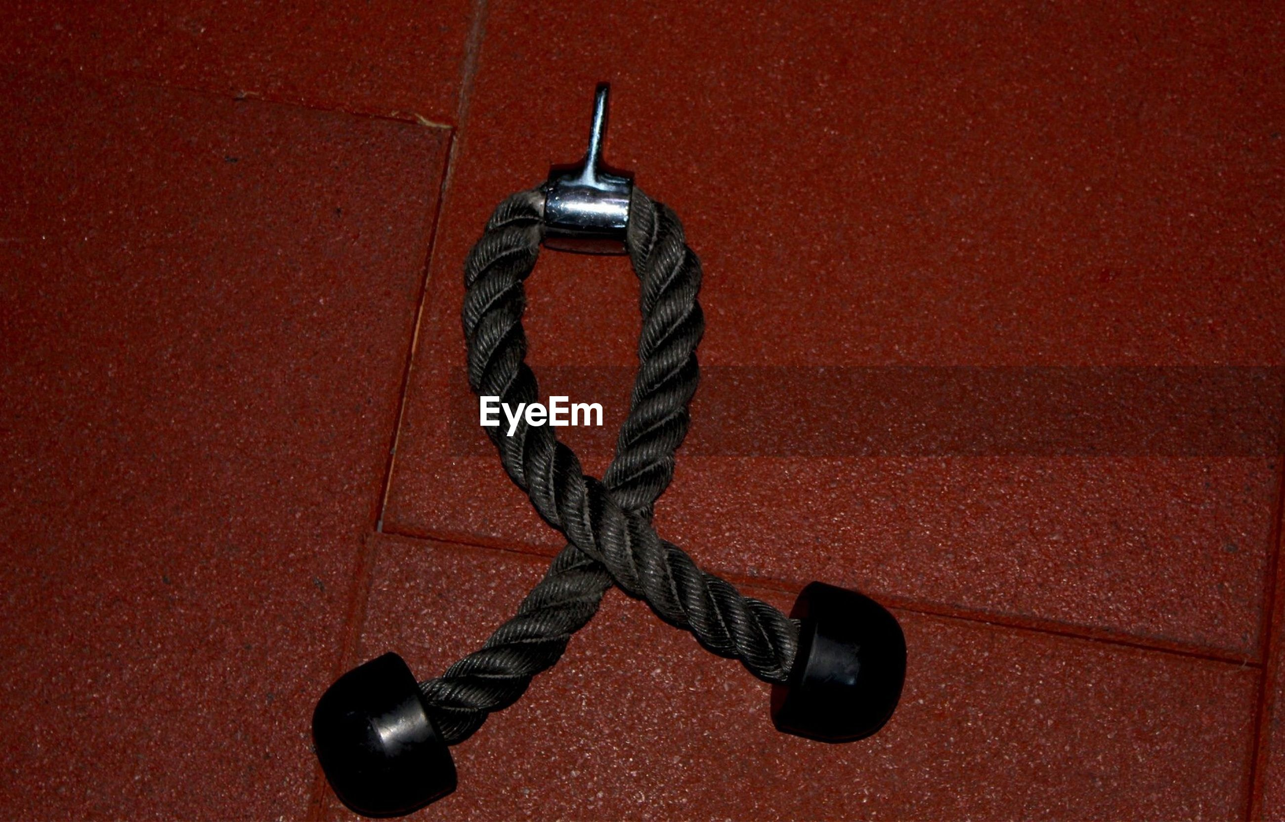 HIGH ANGLE VIEW OF ROPE HANGING ON METAL