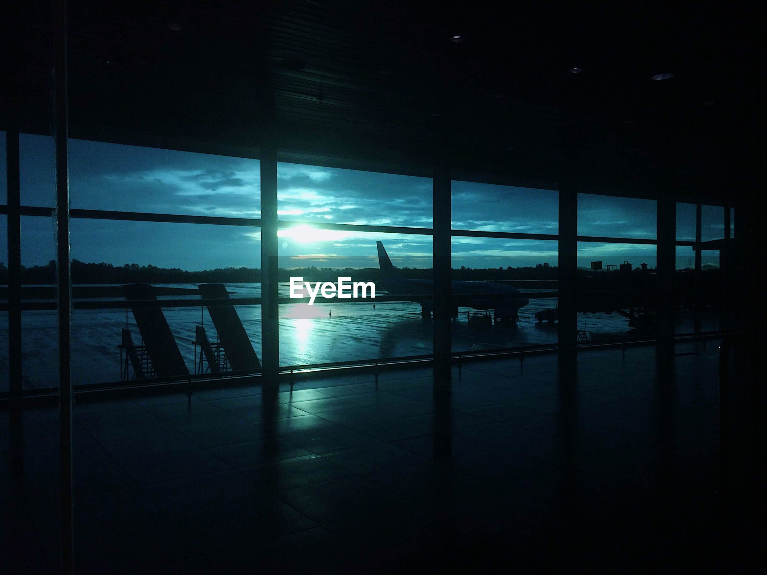 Silhouette airplane against sky seen through glass window