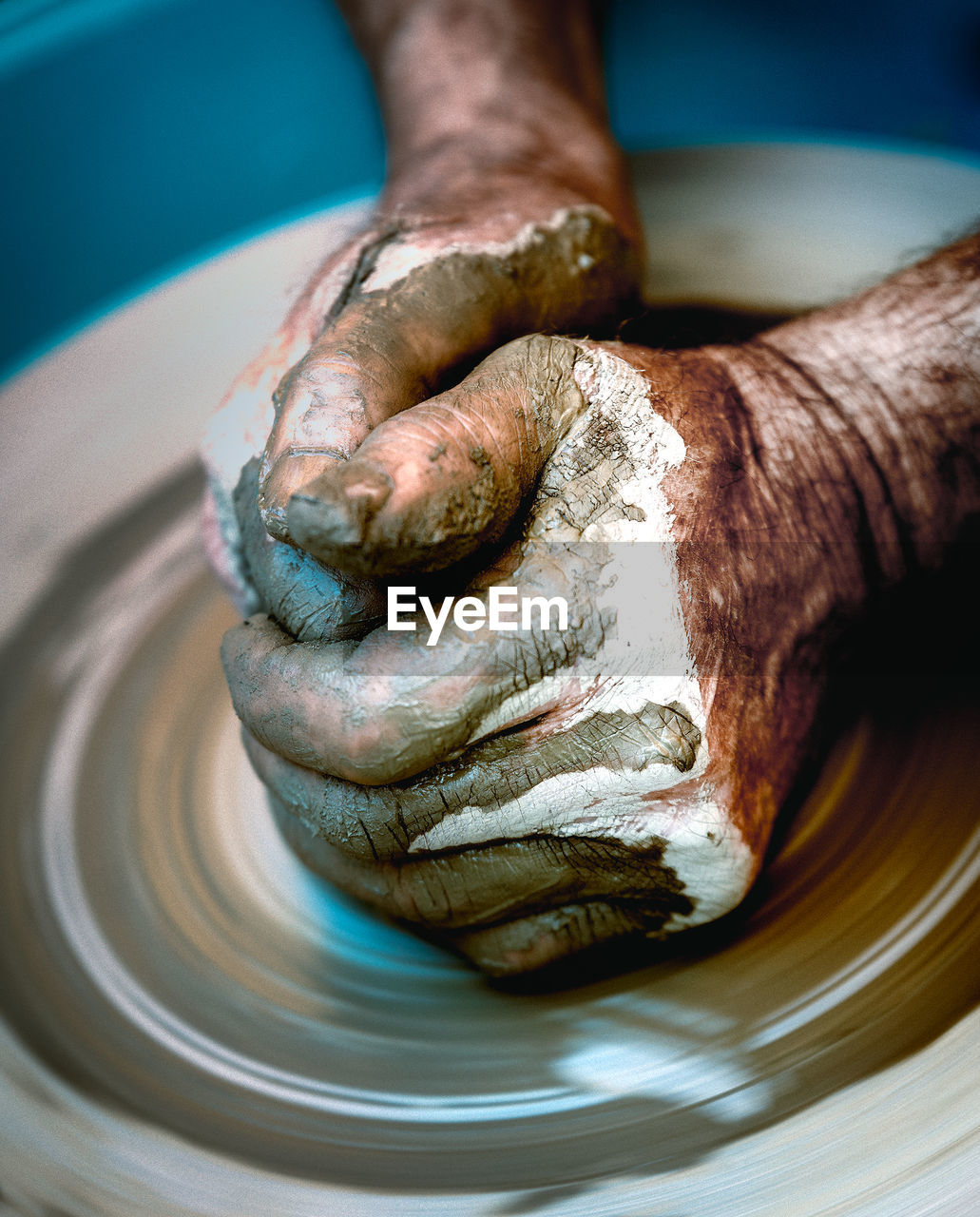 Close-up of human hands making pottery