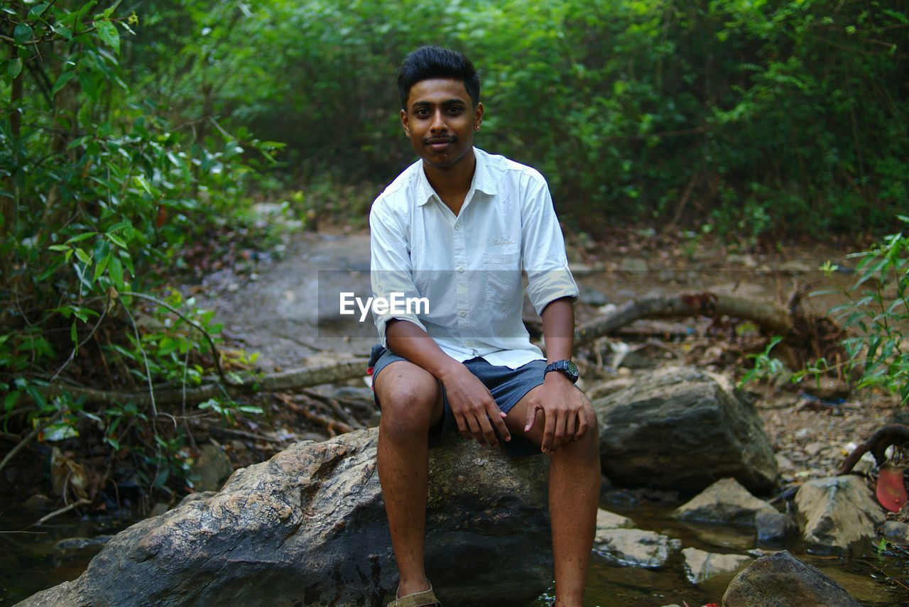 Portrait Of Young Man Sitting In Forest