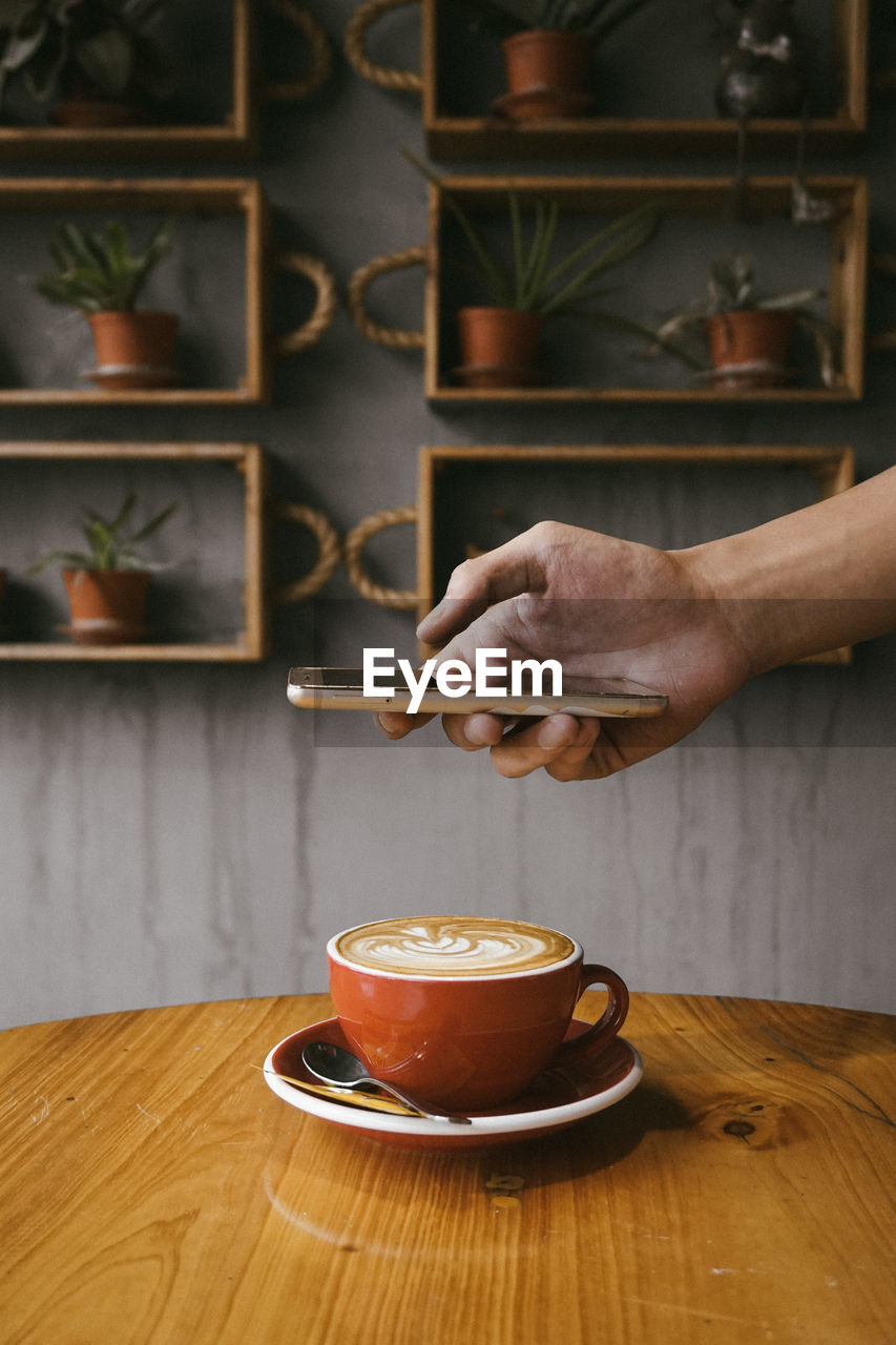 Cropped hand of man photographing coffee on table