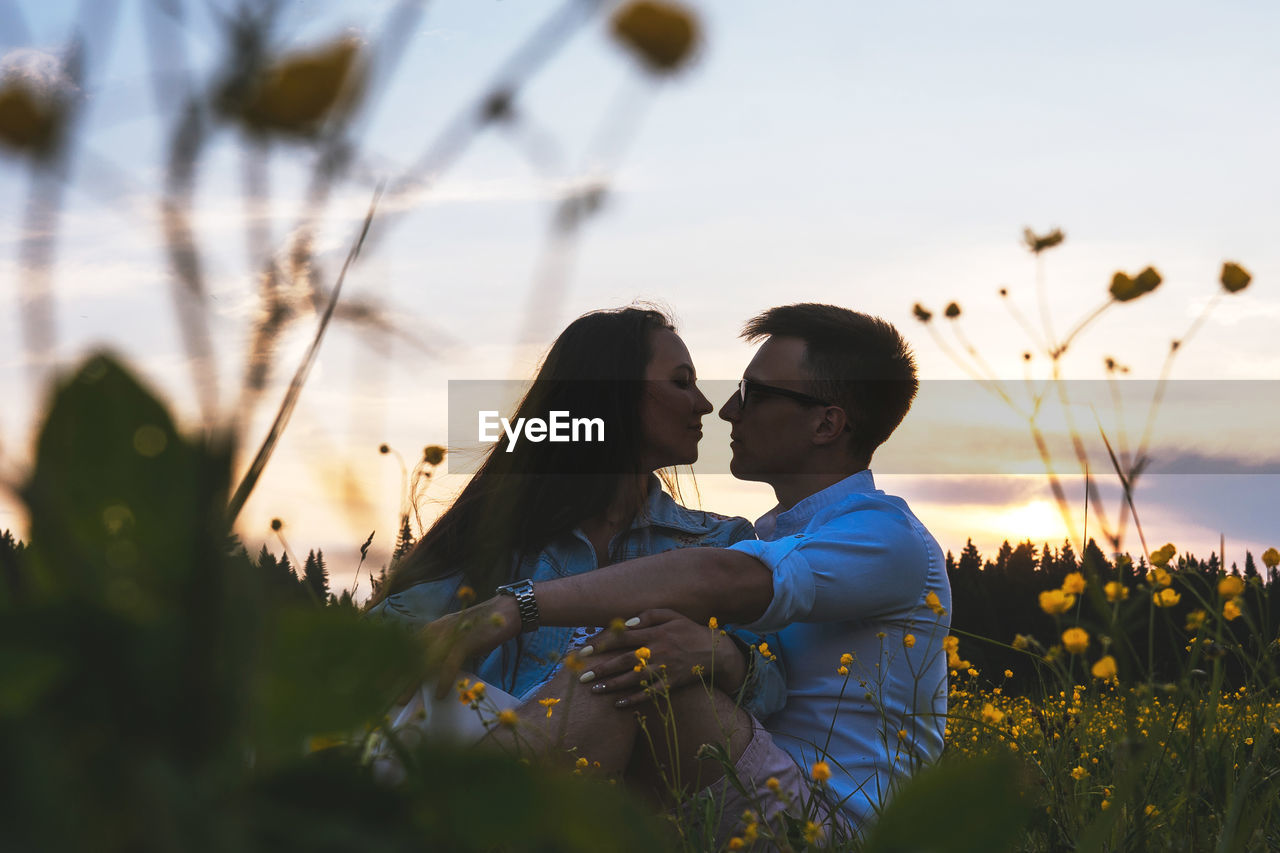 Couple sitting amidst flowering plants against sky during sunset