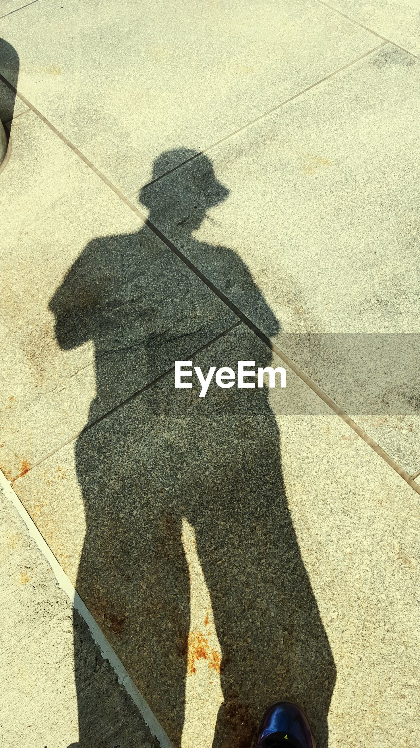 High angle view of person shadow on footpath