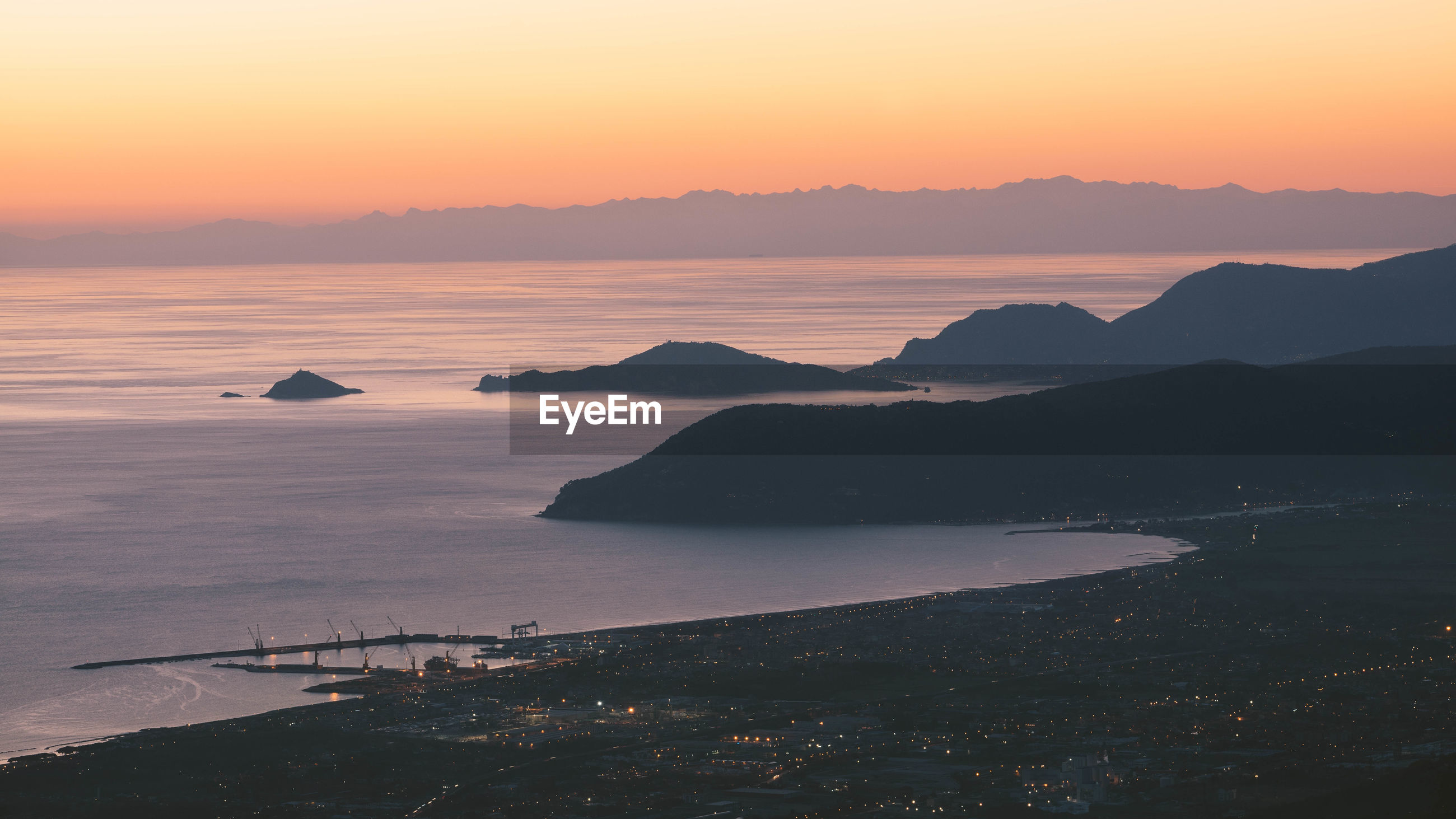 Scenic view of coastline against sky during sunset