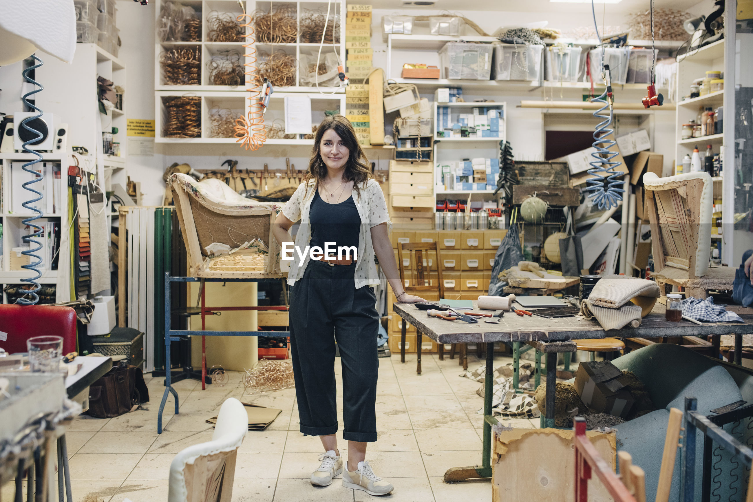 Portrait of confident female upholstery worker standing in workshop