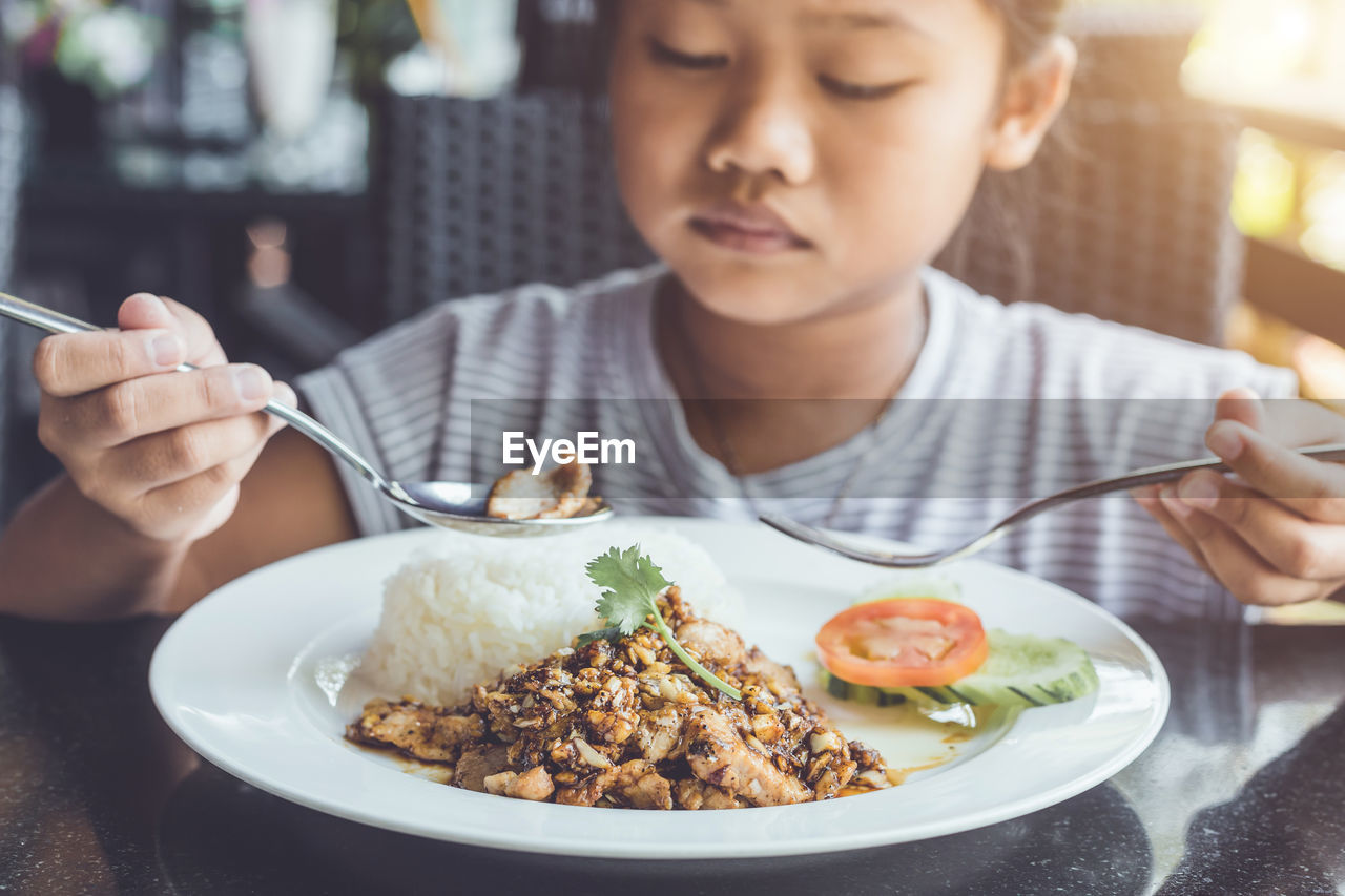 Close-Up Of Girl Eating Food At Table
