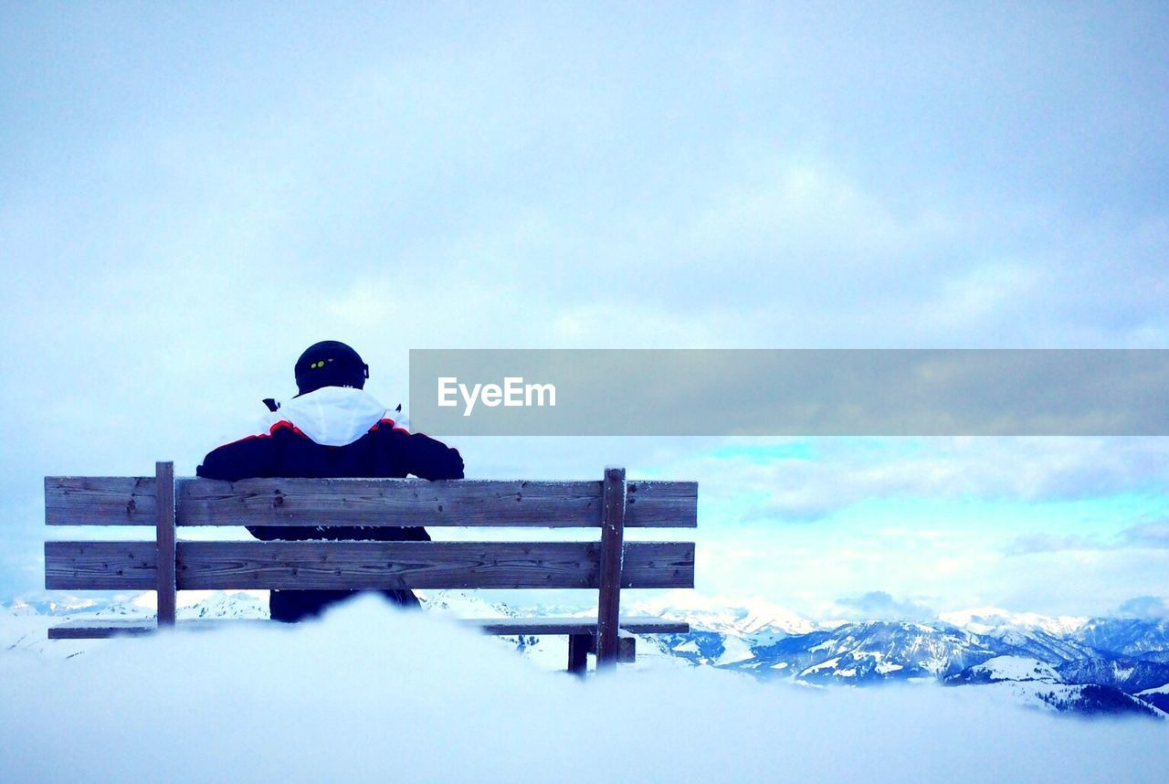 Rear view of person sitting on bench during winter