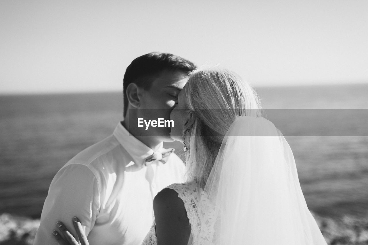 Bride And Groom Kissing Against Clear Sky