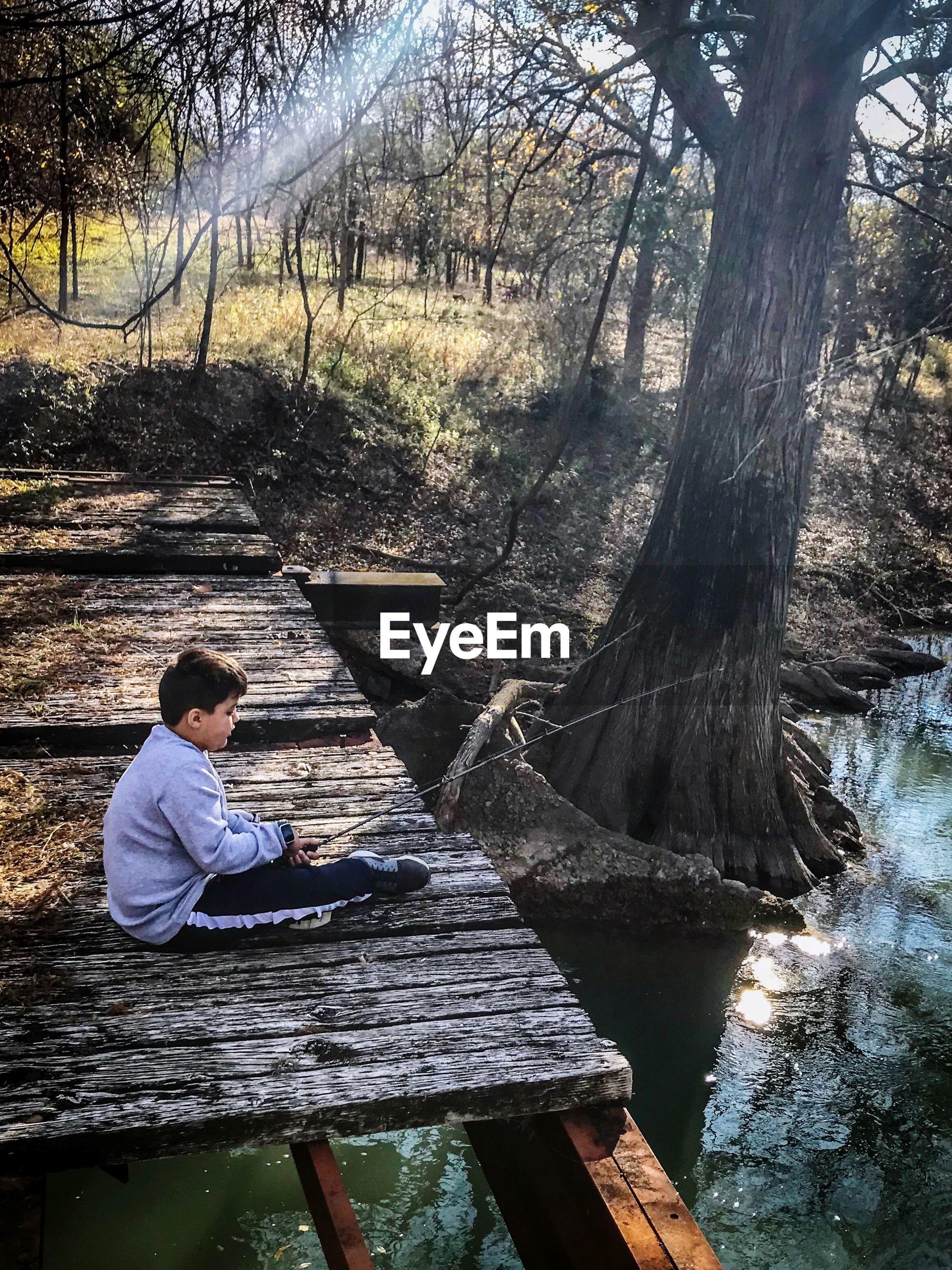 Boy holding fishing rod while sitting on pier over lake