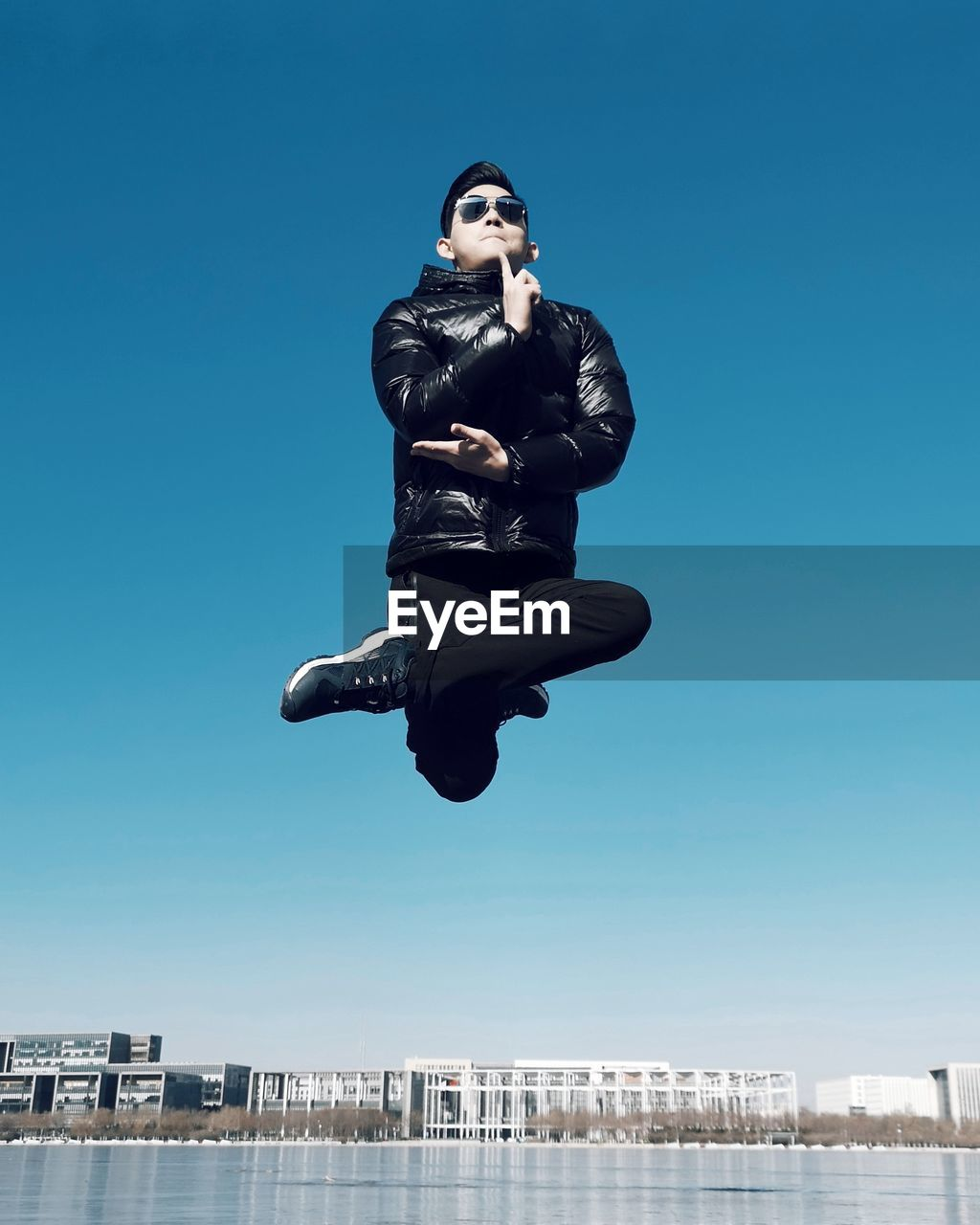 Fashionable man in mid-air over lake against sky in city