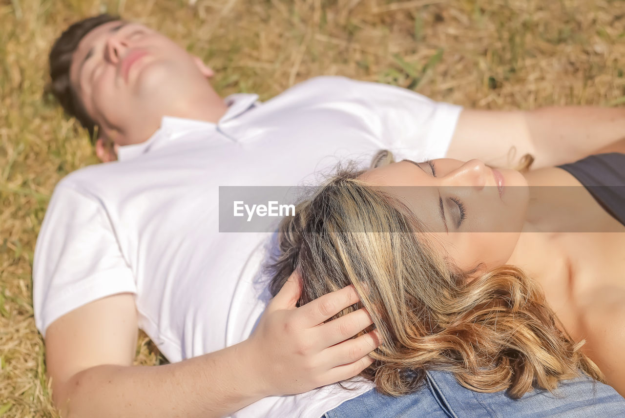 MIDSECTION OF WOMAN WITH BABY LYING DOWN ON THE FLOOR