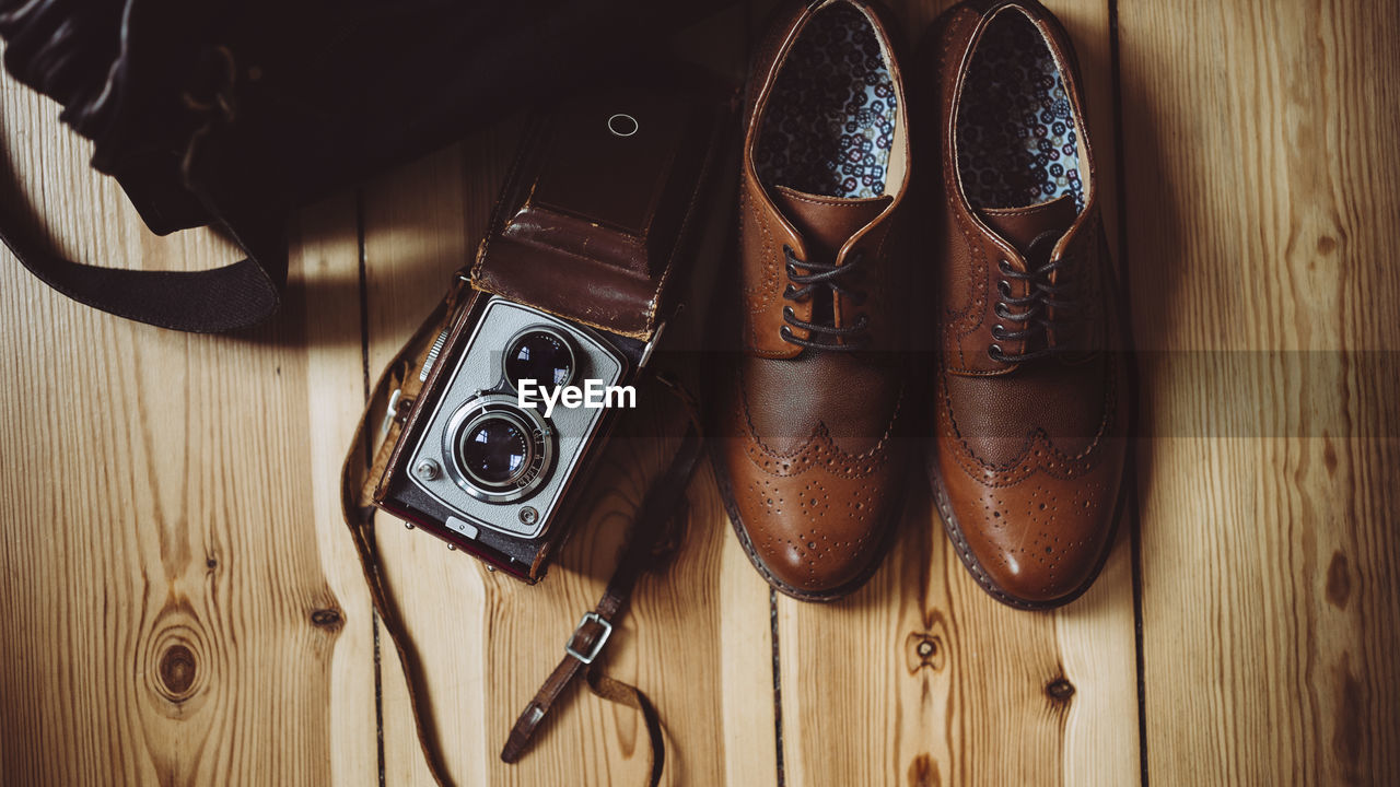 Directly Above Shot Of Shoes And Camera On Floorboard