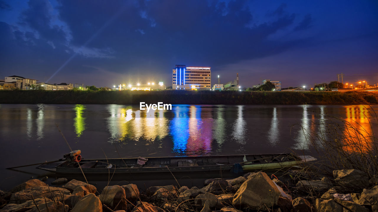 ILLUMINATED BUILDINGS BY LAKE AGAINST SKY
