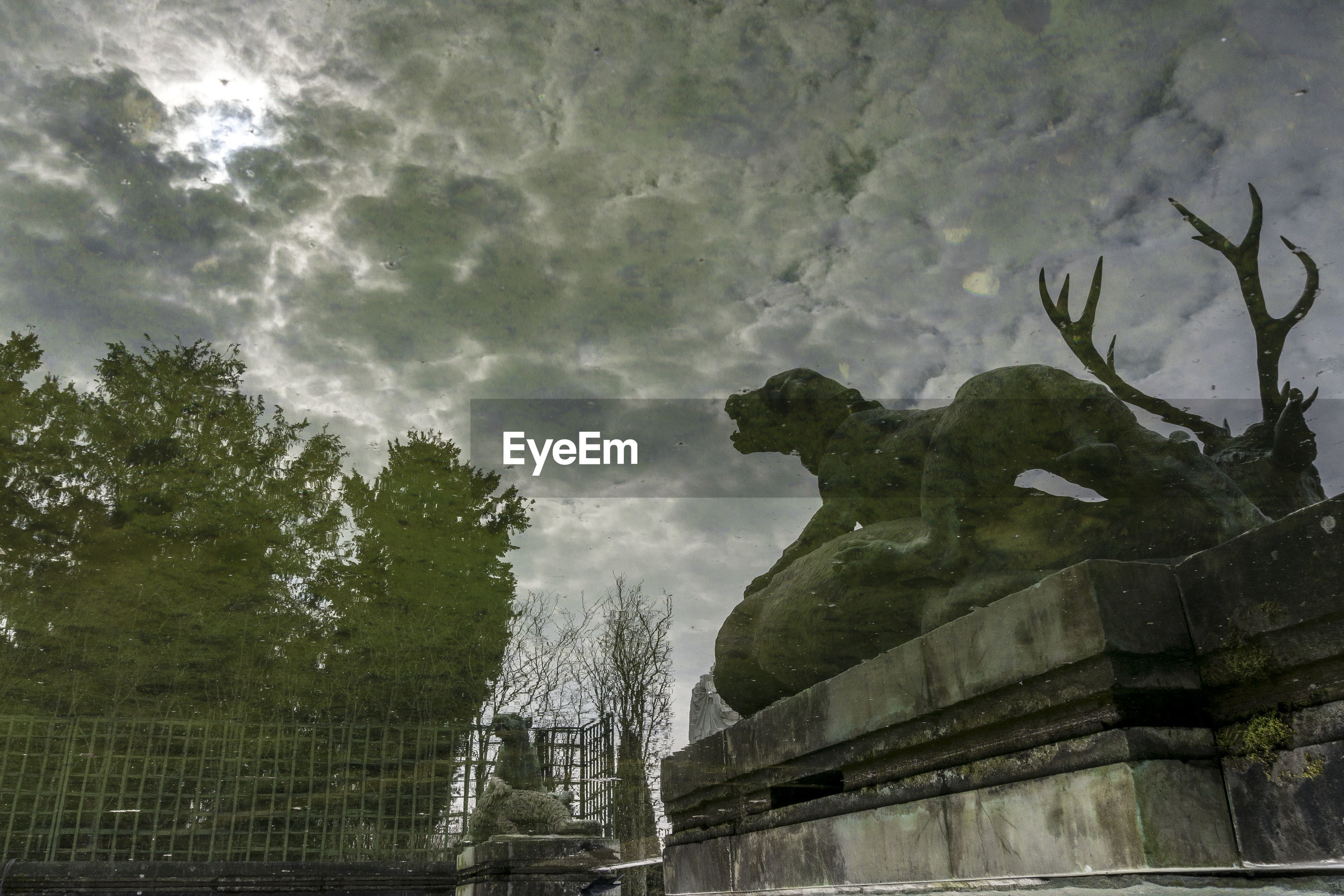Reflection of statue against cloudy sky in water
