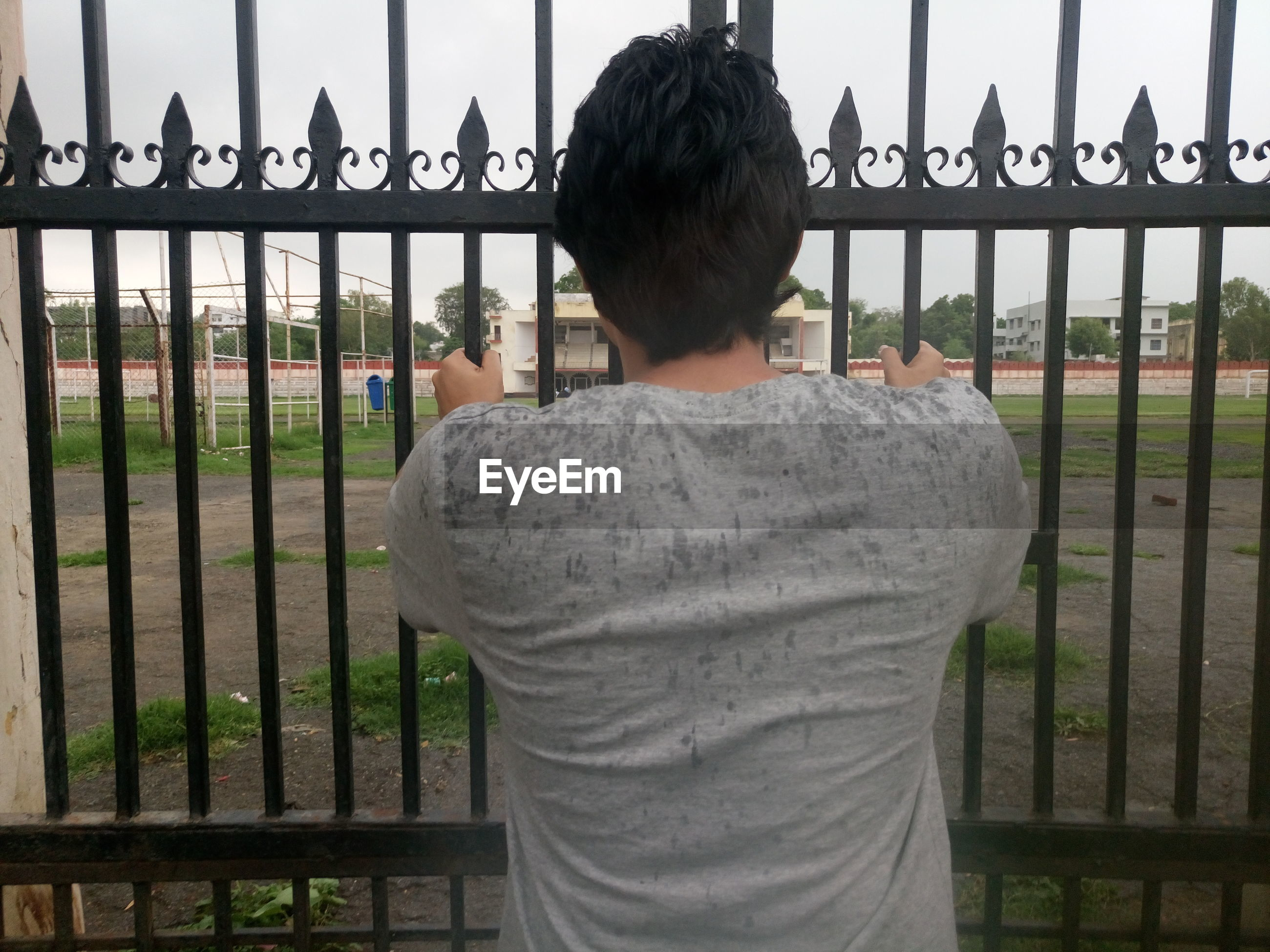Rear view of man holding closed gate against playground