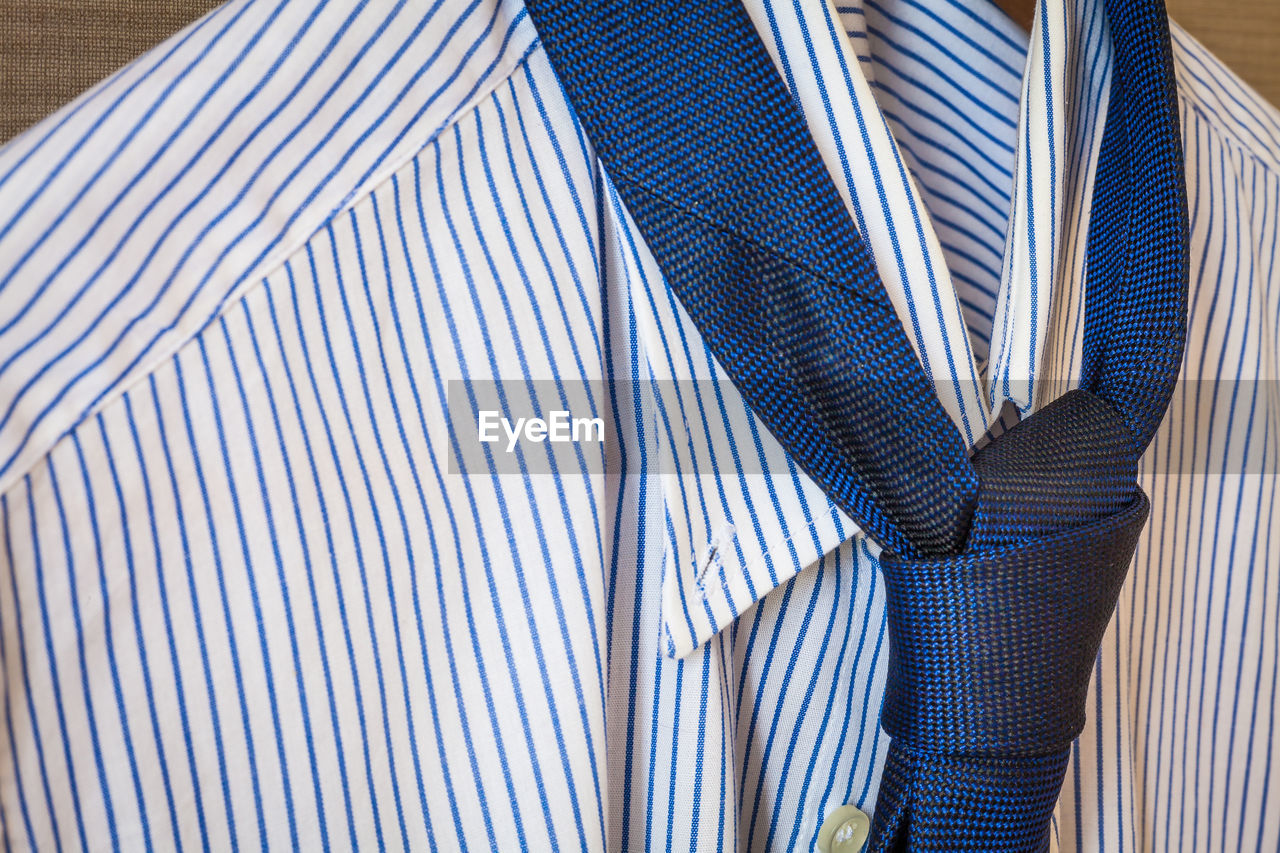 Close-up of shirt and necktie hanging on coathanger
