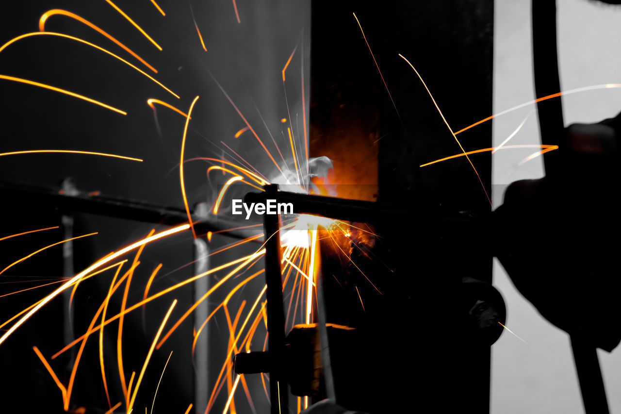 blurred motion, motion, sparks, real people, long exposure, glowing, burning, heat - temperature, indoors, workshop, fire - natural phenomenon, metal, fire, occupation, illuminated, one person, industry, working, welding, metal industry, hand, industrial equipment, steel