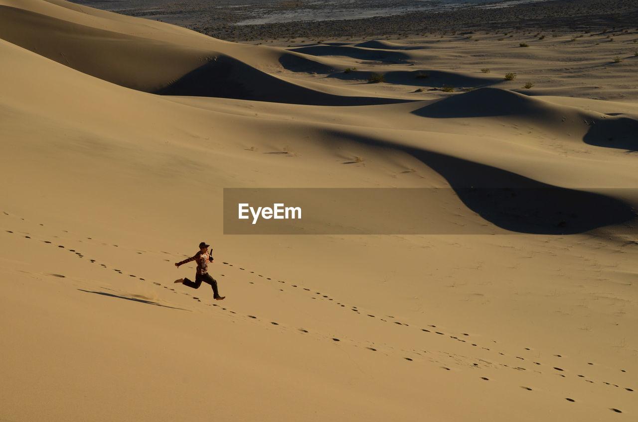 Full Length Of Man Running On Sand