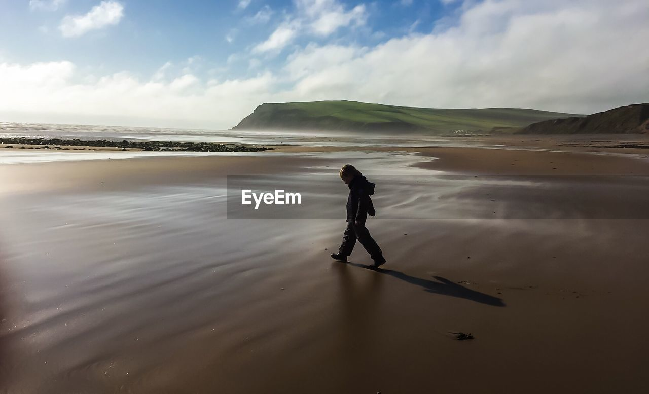 Side View Of Kid Walking On Wet Shore At Beach