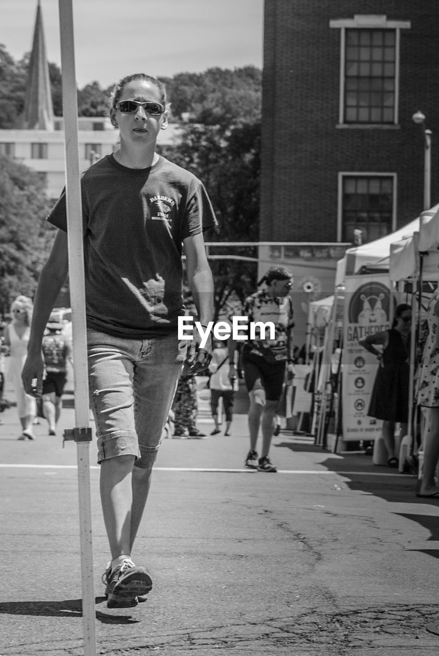 full length, real people, front view, architecture, glasses, one person, lifestyles, leisure activity, casual clothing, built structure, portrait, incidental people, young men, day, young adult, looking at camera, city, building exterior, standing, fashion, outdoors