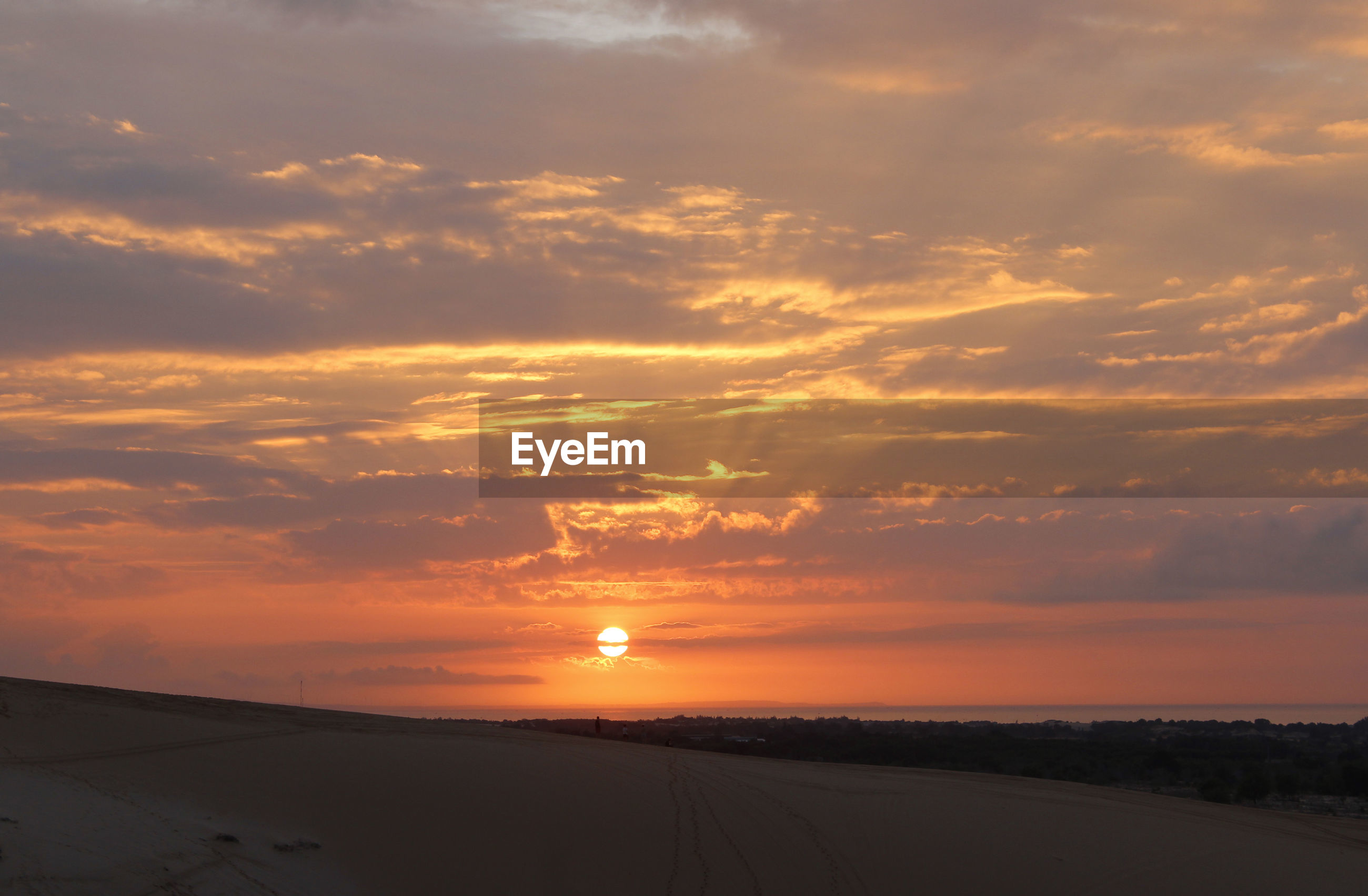 SCENIC VIEW OF SUNSET OVER LANDSCAPE AGAINST SKY