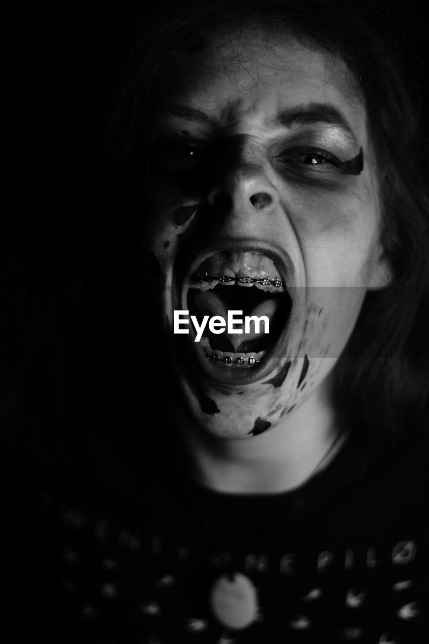 one person, horror, shouting, mouth open, spooky, headshot, looking at camera, screaming, young adult, halloween, shock, real people, night, black background, portrait, young women, indoors, close-up, one young woman only, one woman only, people, adult, adults only
