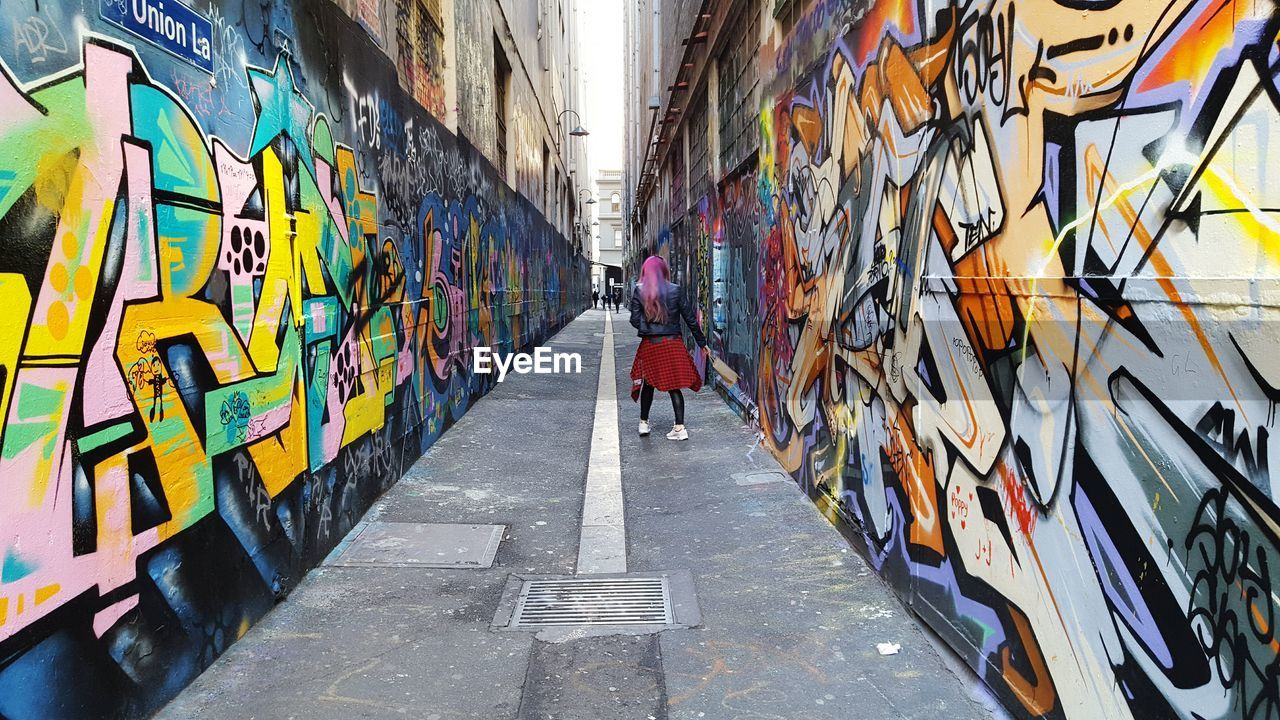 Rear view of woman walking at alley amidst graffiti wall in city