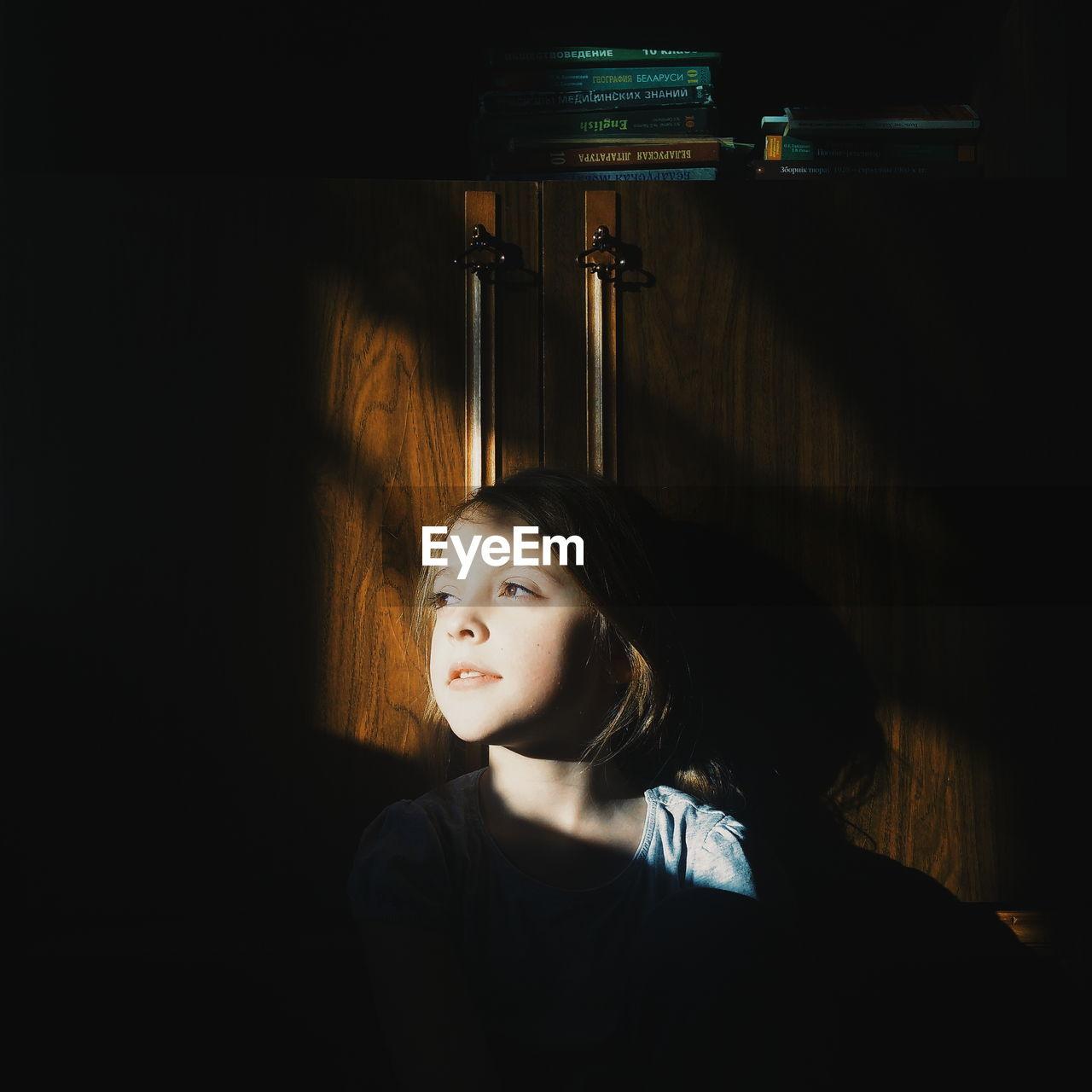 Thoughtful Girl Sitting In Darkroom