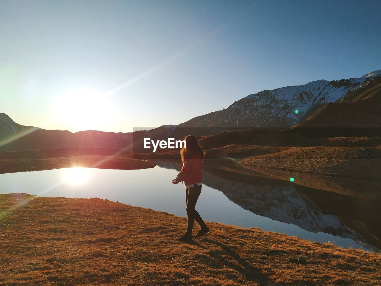 sky, mountain, beauty in nature, real people, one person, water, tranquility, lifestyles, leisure activity, sunlight, scenics - nature, tranquil scene, nature, sun, non-urban scene, full length, standing, mountain range, lens flare, outdoors, human arm