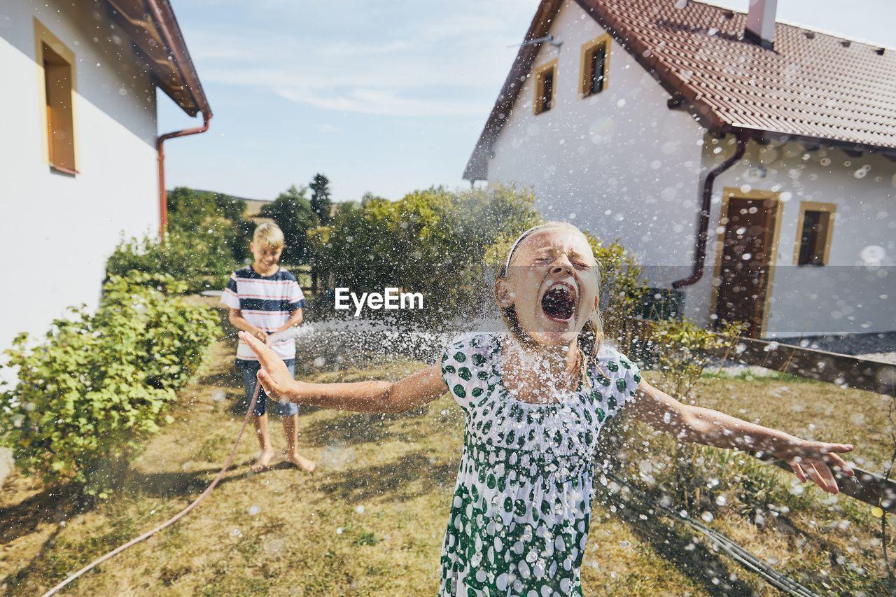 Boy Spraying Water On Sister Standing In Yard