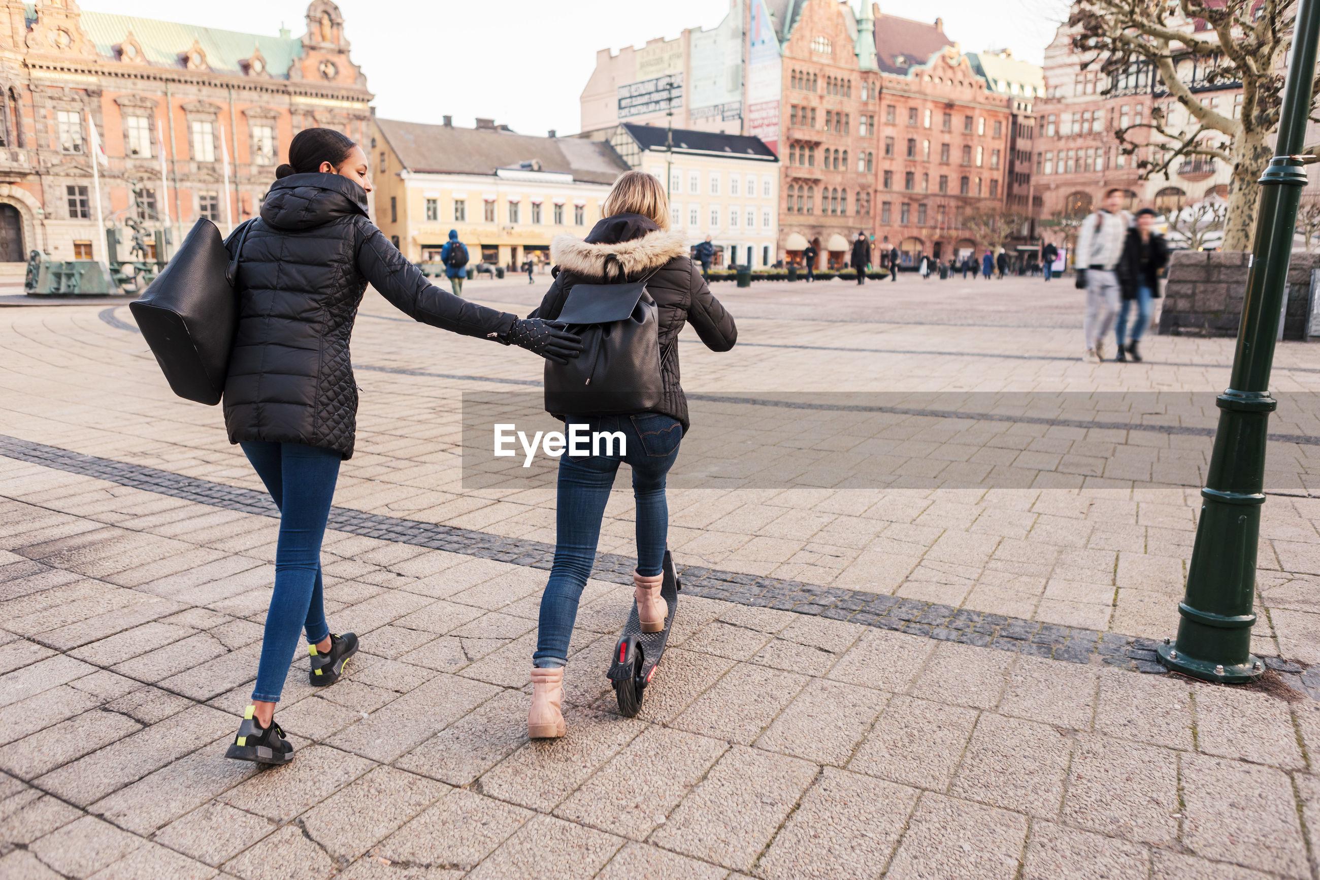 FULL LENGTH REAR VIEW OF WOMEN WALKING ON FOOTPATH IN CITY