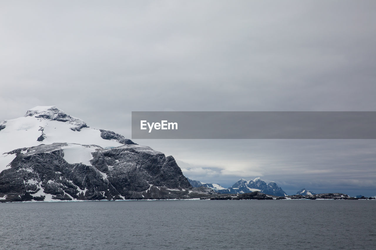 sky, scenics - nature, mountain, water, cold temperature, beauty in nature, environment, winter, glacier, waterfront, tranquil scene, nature, tranquility, no people, landscape, sea, ice, snow, snowcapped mountain, iceberg