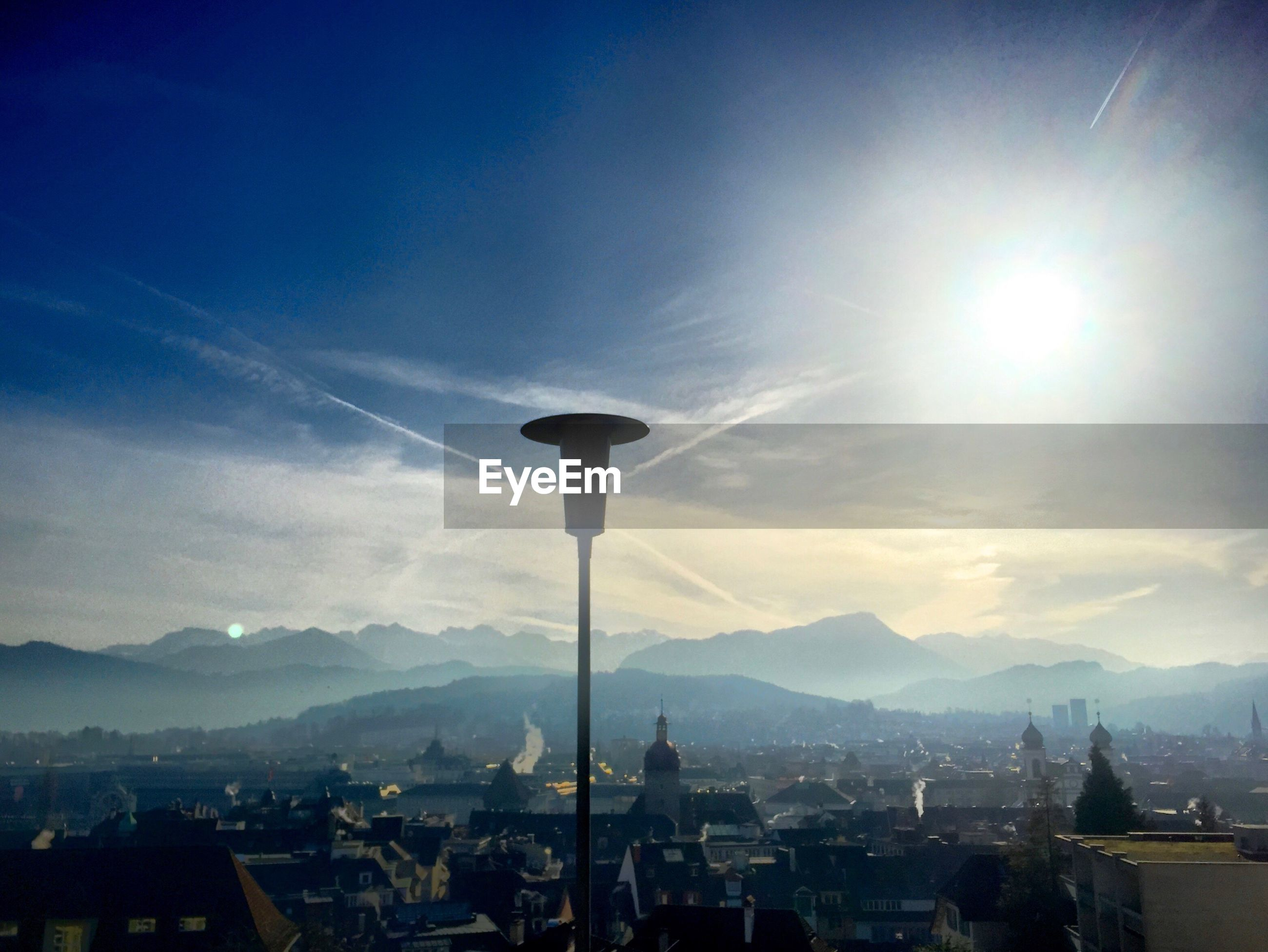 Street light against cityscape by silhouette mountains on sunny day
