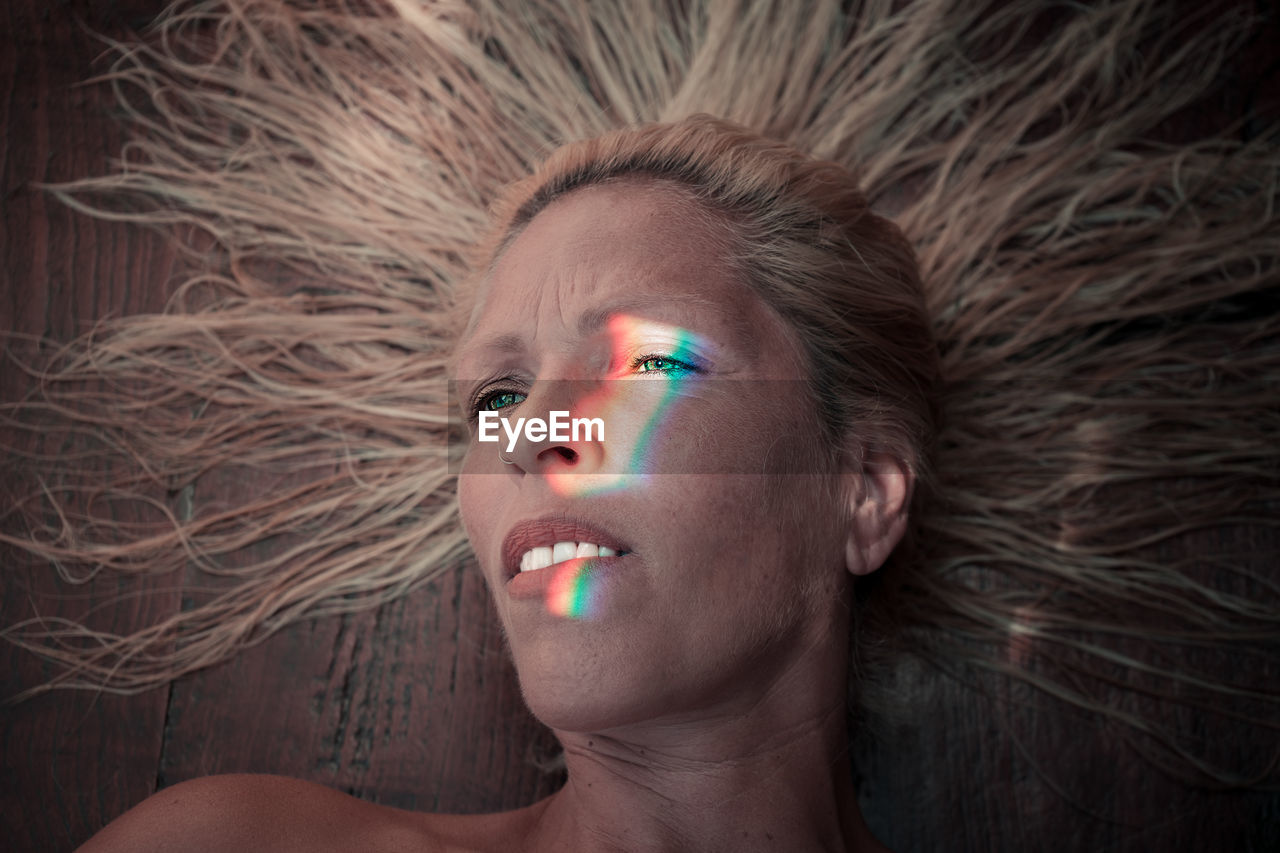 Spectrum On Face Of Woman Lying On Wood