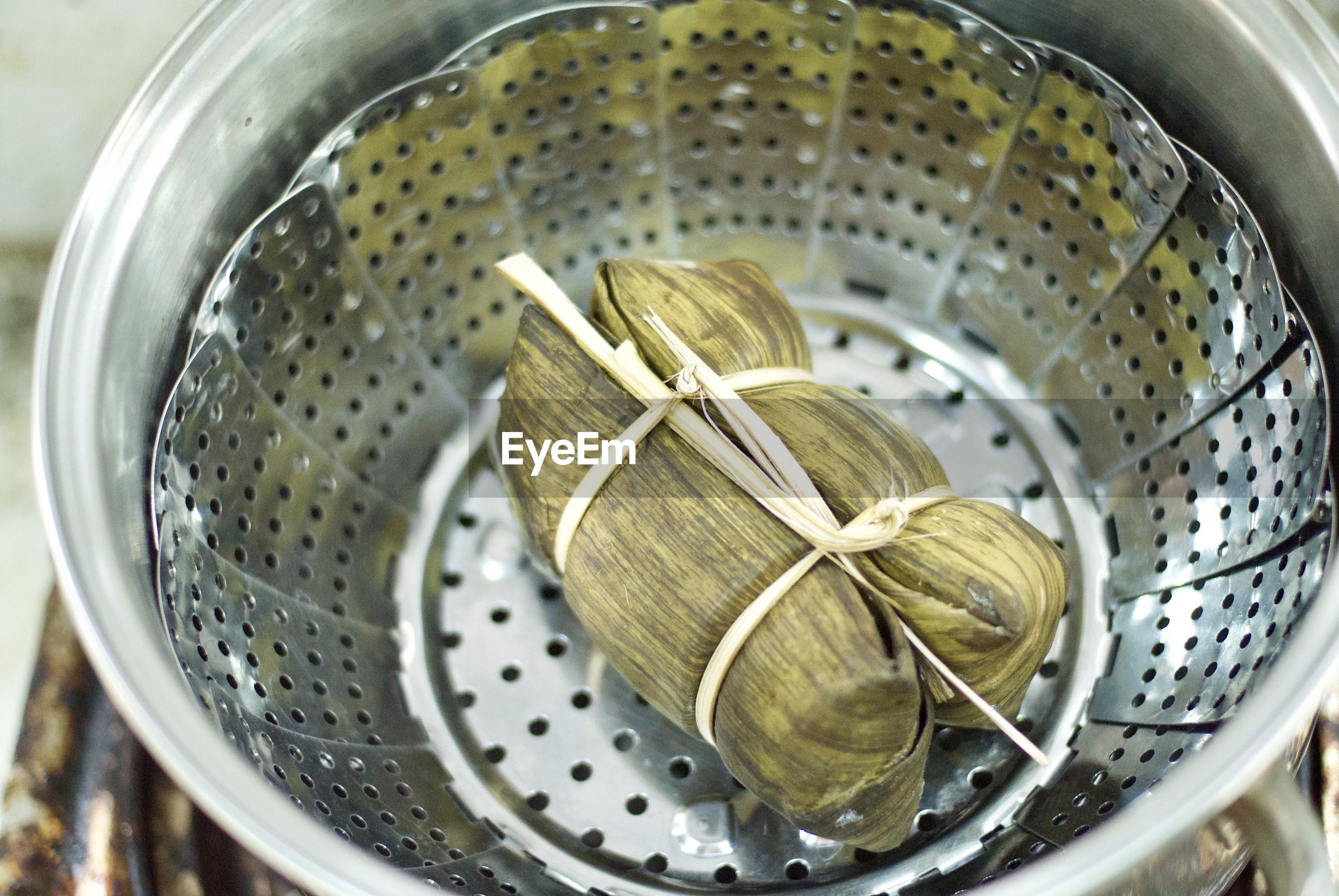High angle view of tied leaves in colander