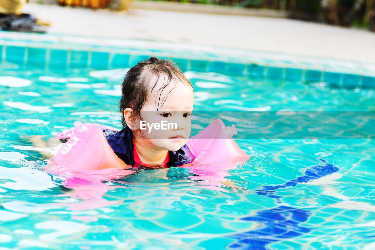 Cute girl with water wings swimming in pool