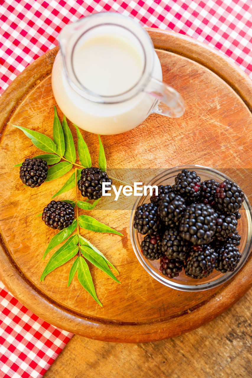 food and drink, food, healthy eating, fruit, freshness, berry fruit, table, wellbeing, indoors, blackberry - fruit, high angle view, still life, no people, blueberry, drink, refreshment, leaf, plant part, kitchen utensil, cup, crockery, ripe