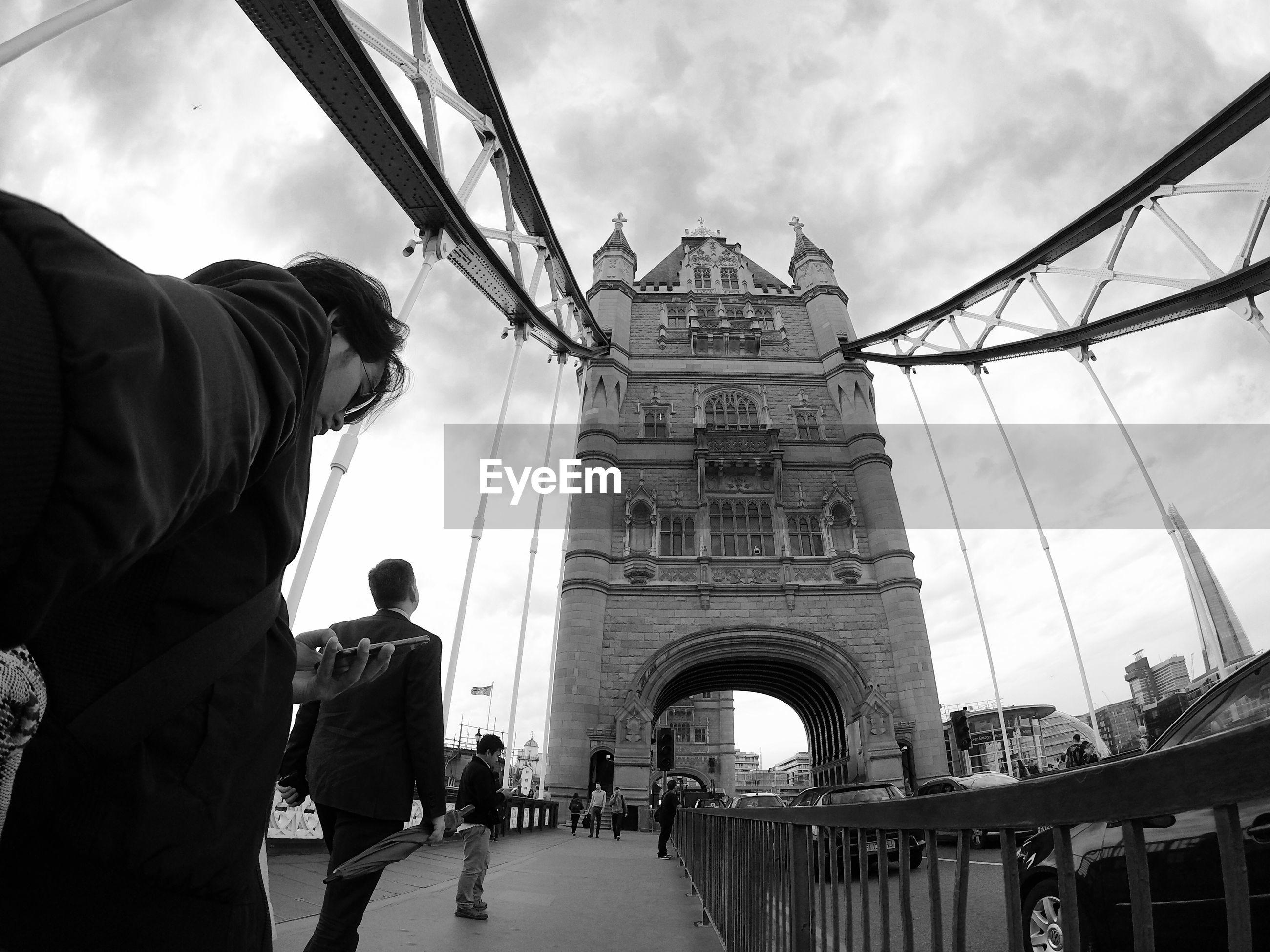People on tower bridge against sky