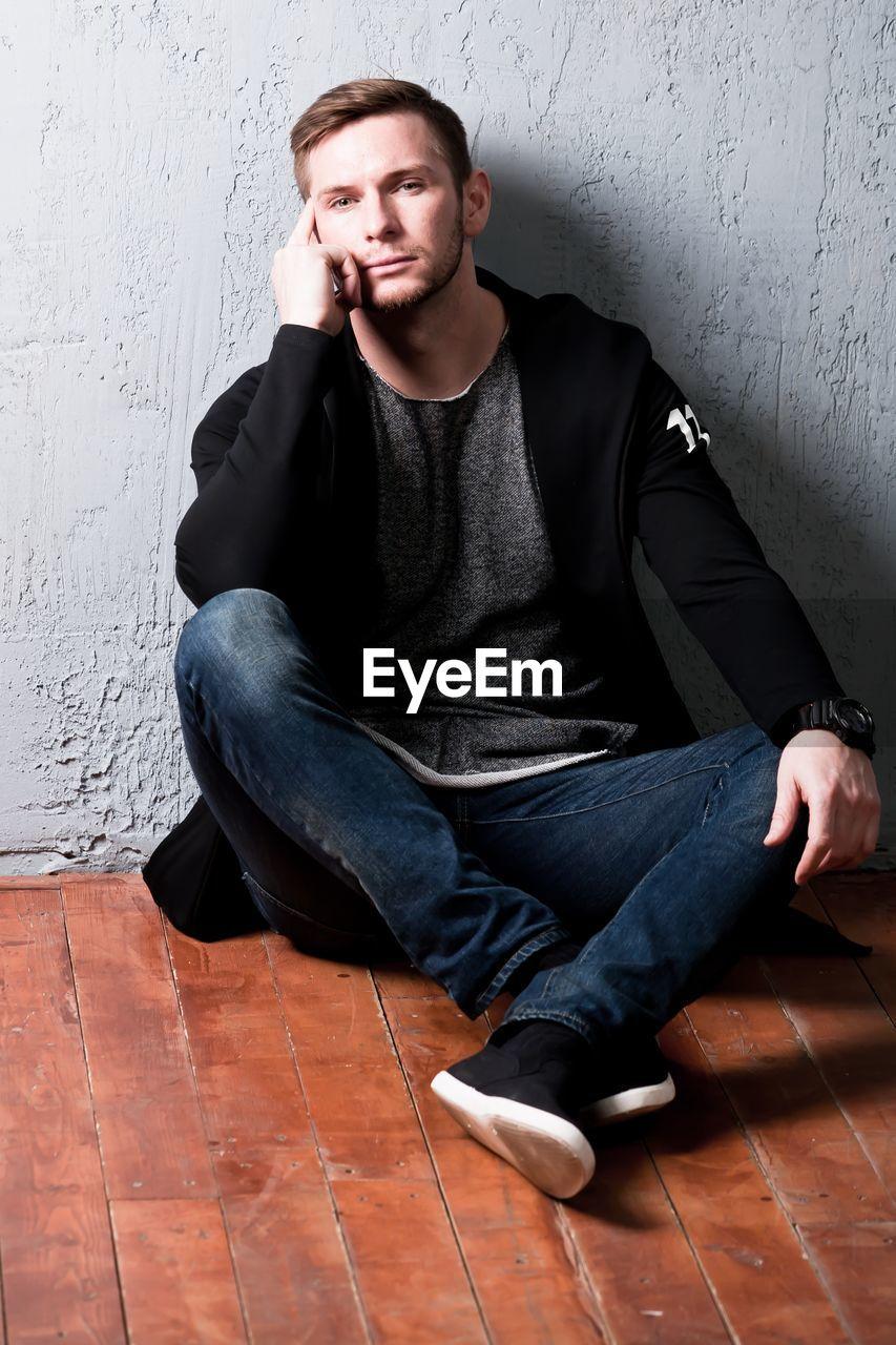 Portrait of handsome mid adult man sitting on floorboard