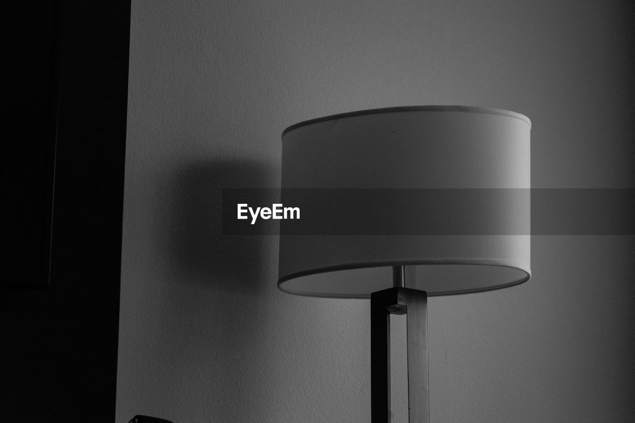 lighting equipment, lamp shade, electric lamp, indoors, wall - building feature, floor lamp, home interior, no people, technology, electricity, illuminated, close-up, electric light, wall, domestic room, connection, shadow, light, fuel and power generation, copy space, power supply