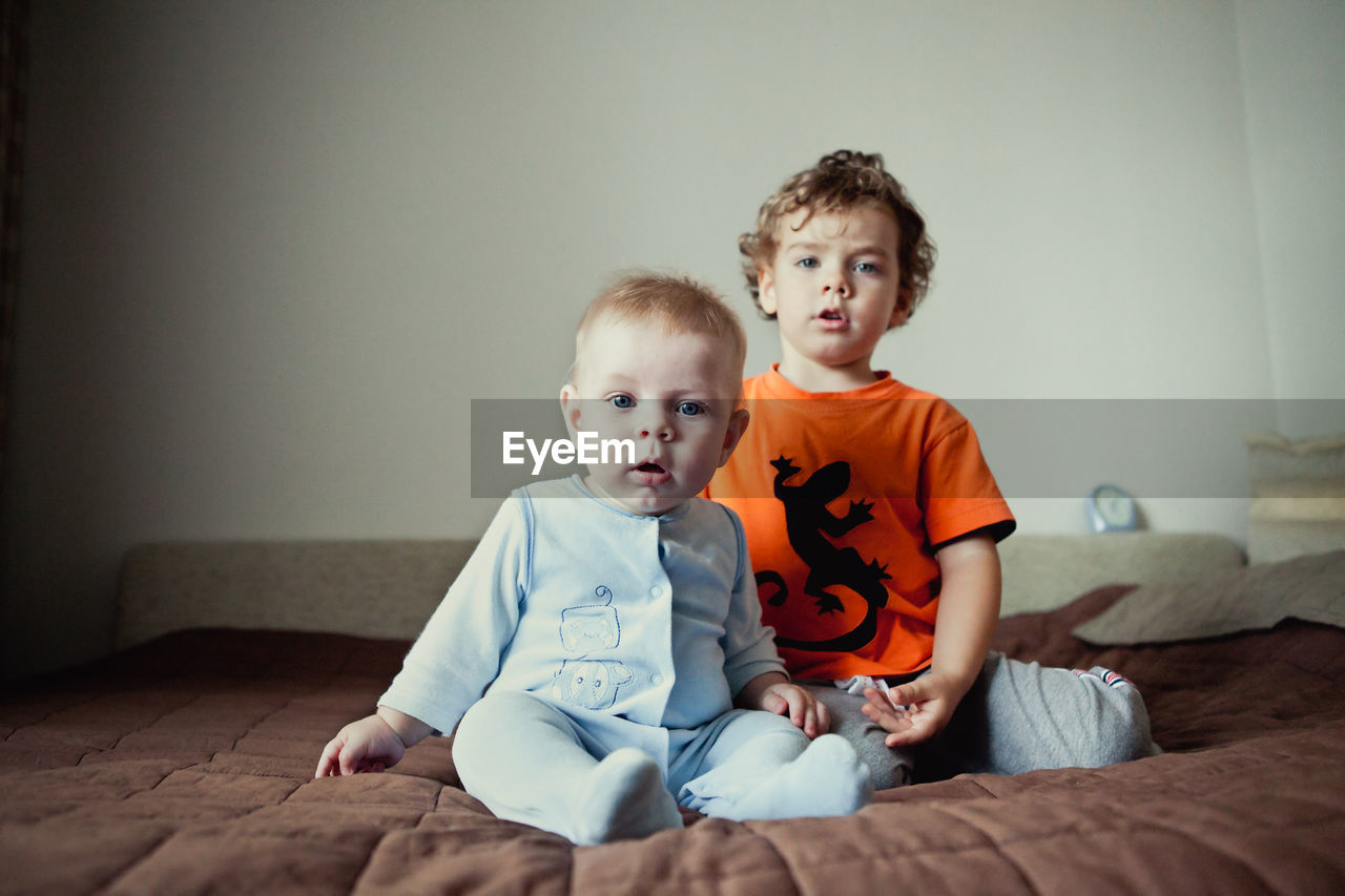 Cute little boys brothers sitting next to each other.