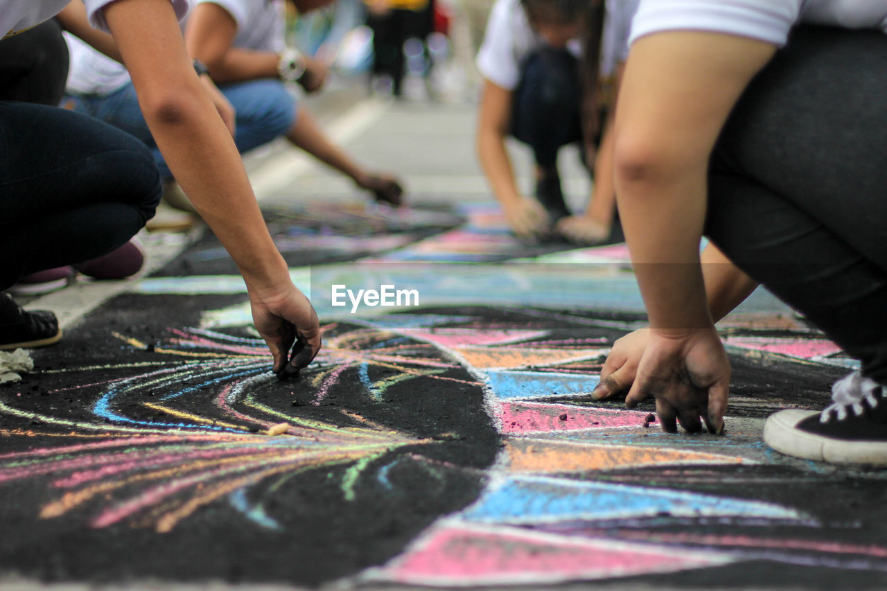 Low section of people drawing on footpath