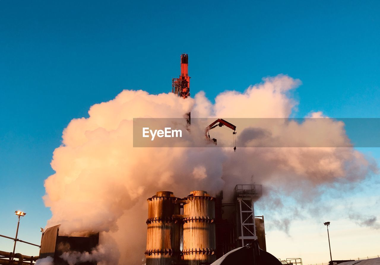 sky, smoke - physical structure, pollution, industry, factory, nature, building exterior, cloud - sky, low angle view, emitting, environmental issues, smoke stack, flying, blue, built structure, day, air pollution, motion, no people, architecture, outdoors, fumes