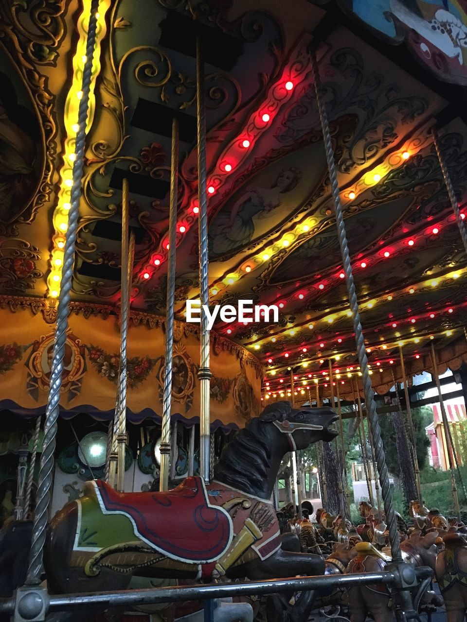 illuminated, lighting equipment, amusement park, amusement park ride, hanging, night, carousel, arts culture and entertainment, decoration, low angle view, animal representation, representation, no people, built structure, multi colored, architecture, glowing, electricity, variation, carousel horses, electric lamp
